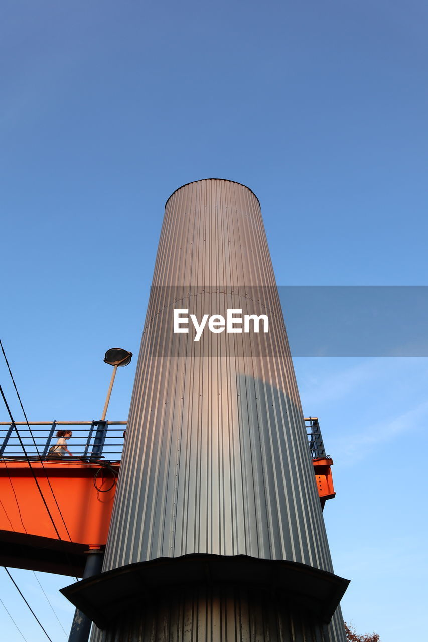 sky, built structure, architecture, low angle view, blue, day, nature, building exterior, no people, factory, clear sky, industry, outdoors, sunlight, copy space, metal, storage tank, modern, tall - high, building