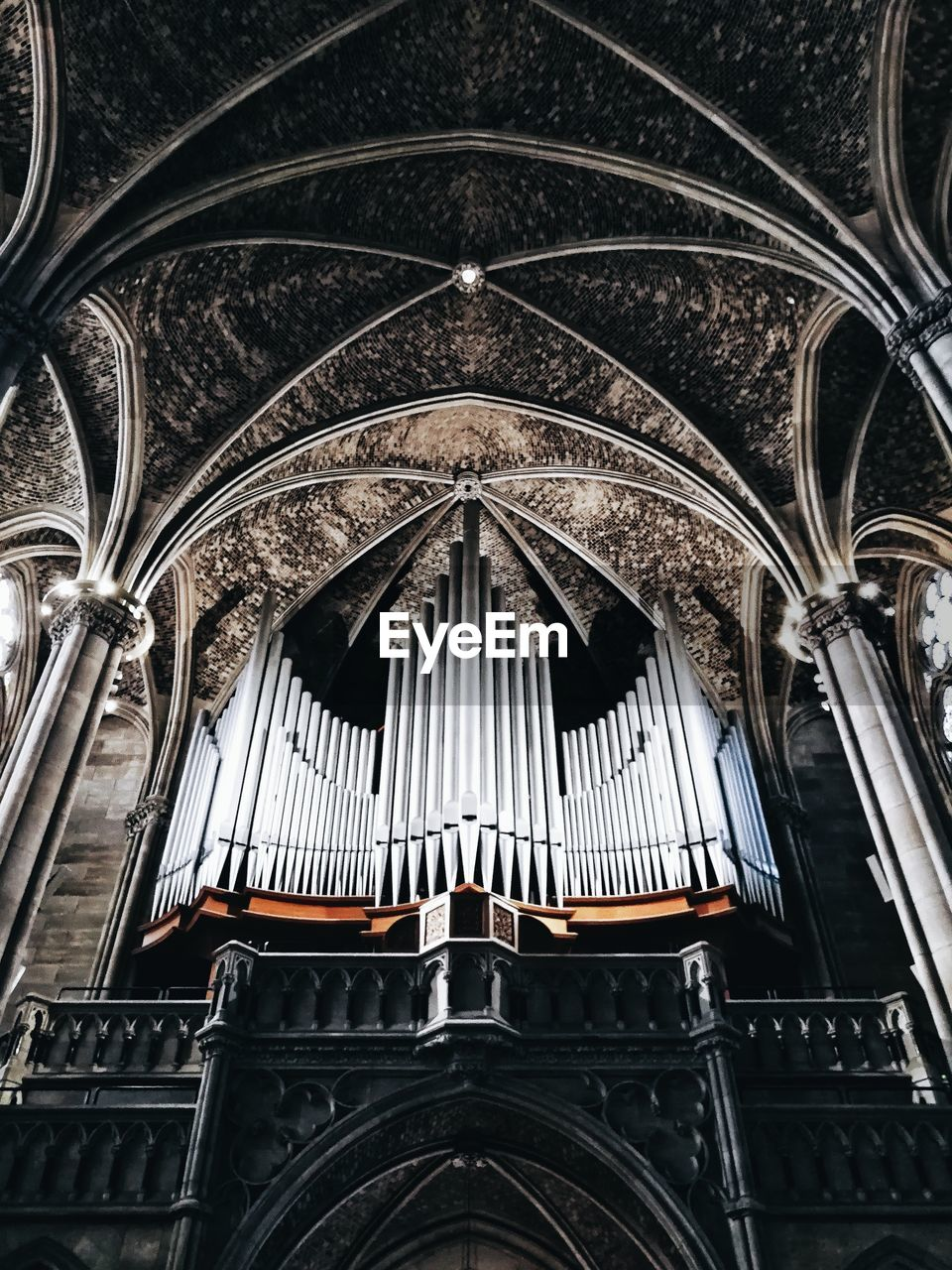 low angle view, built structure, architecture, place of worship, religion, no people, belief, indoors, spirituality, building, arch, pipe organ, music, musical instrument, pattern, ceiling, architecture and art, ornate, gothic style