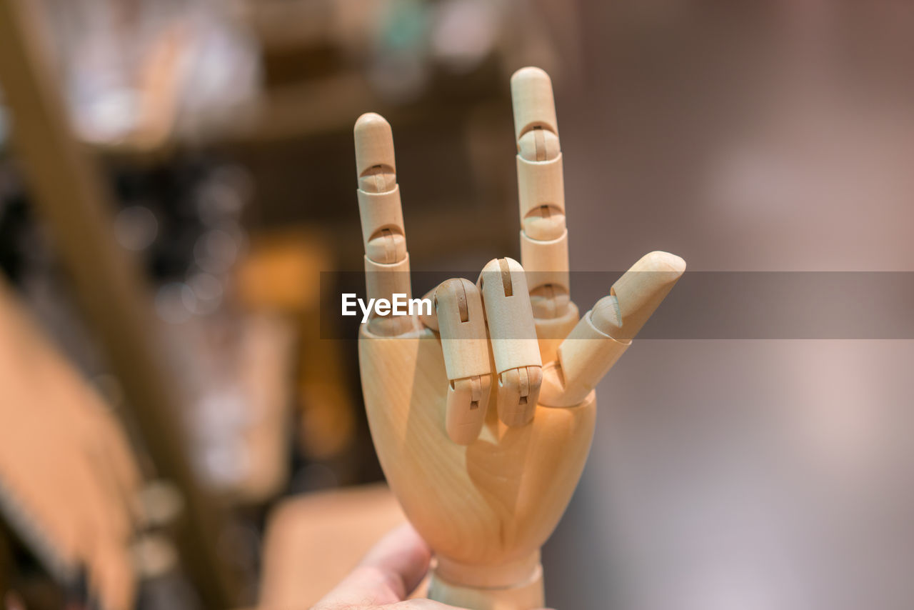 Close-Up Of Wooden Hand With Horn Gesture