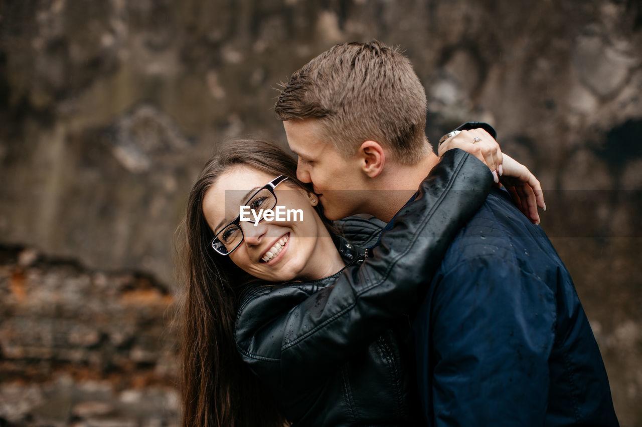 Loving boyfriend whispering in cheerful girlfriend ear outdoors
