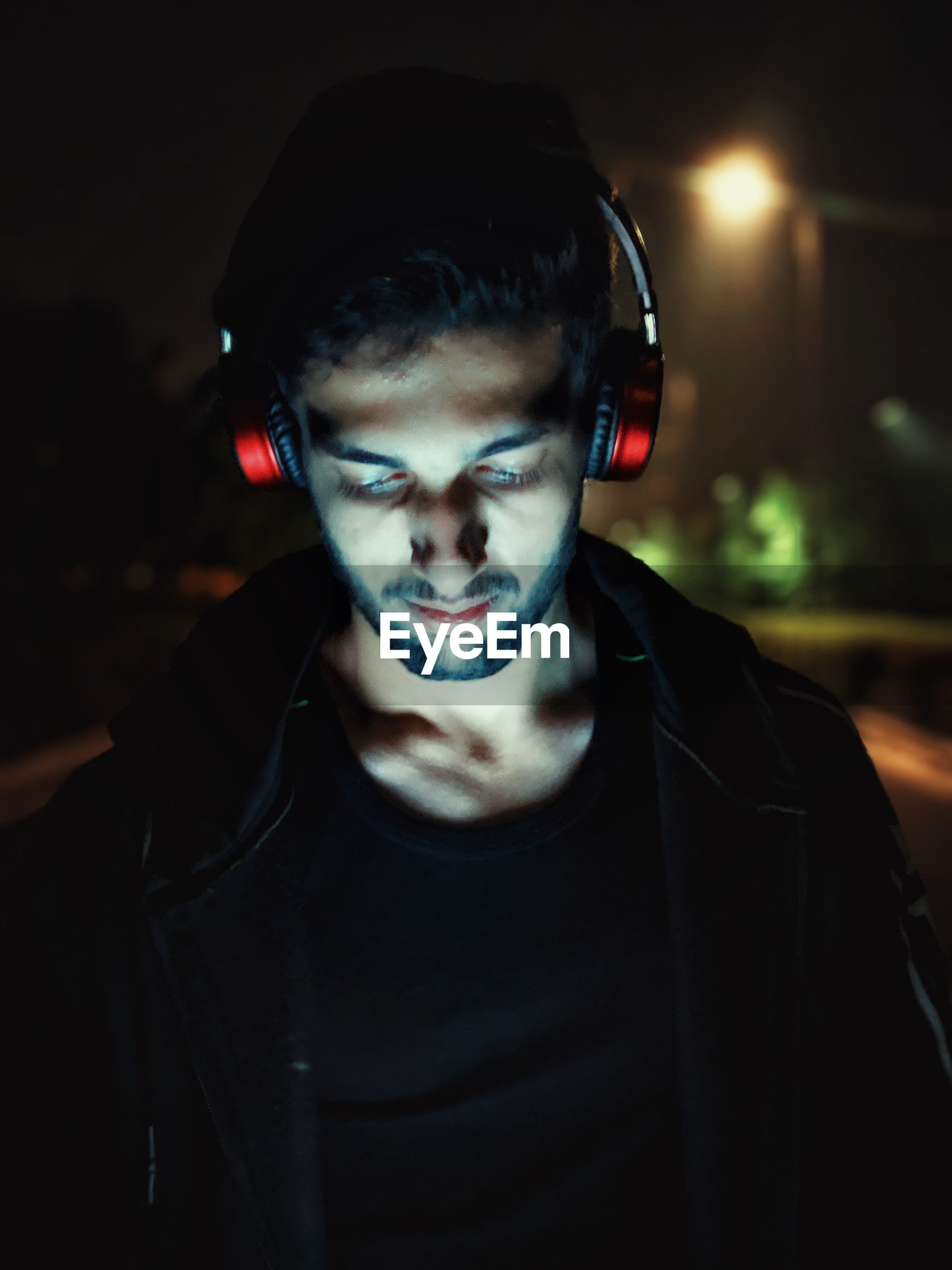Young man using headphones at night