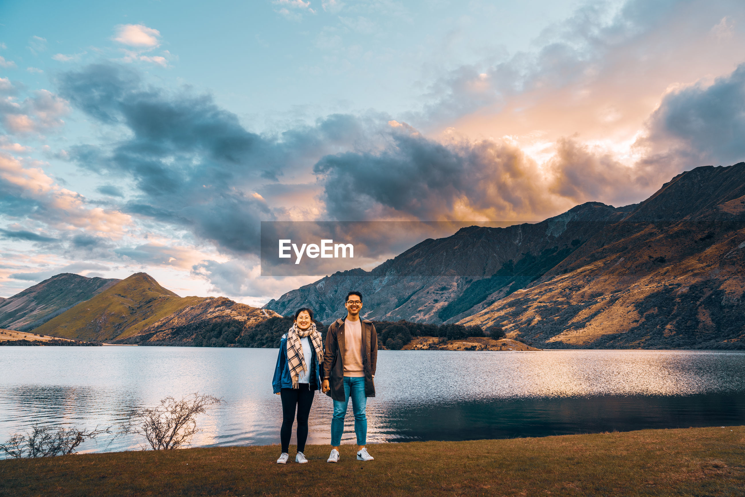 REAR VIEW OF FRIENDS STANDING ON LAKE AGAINST MOUNTAINS