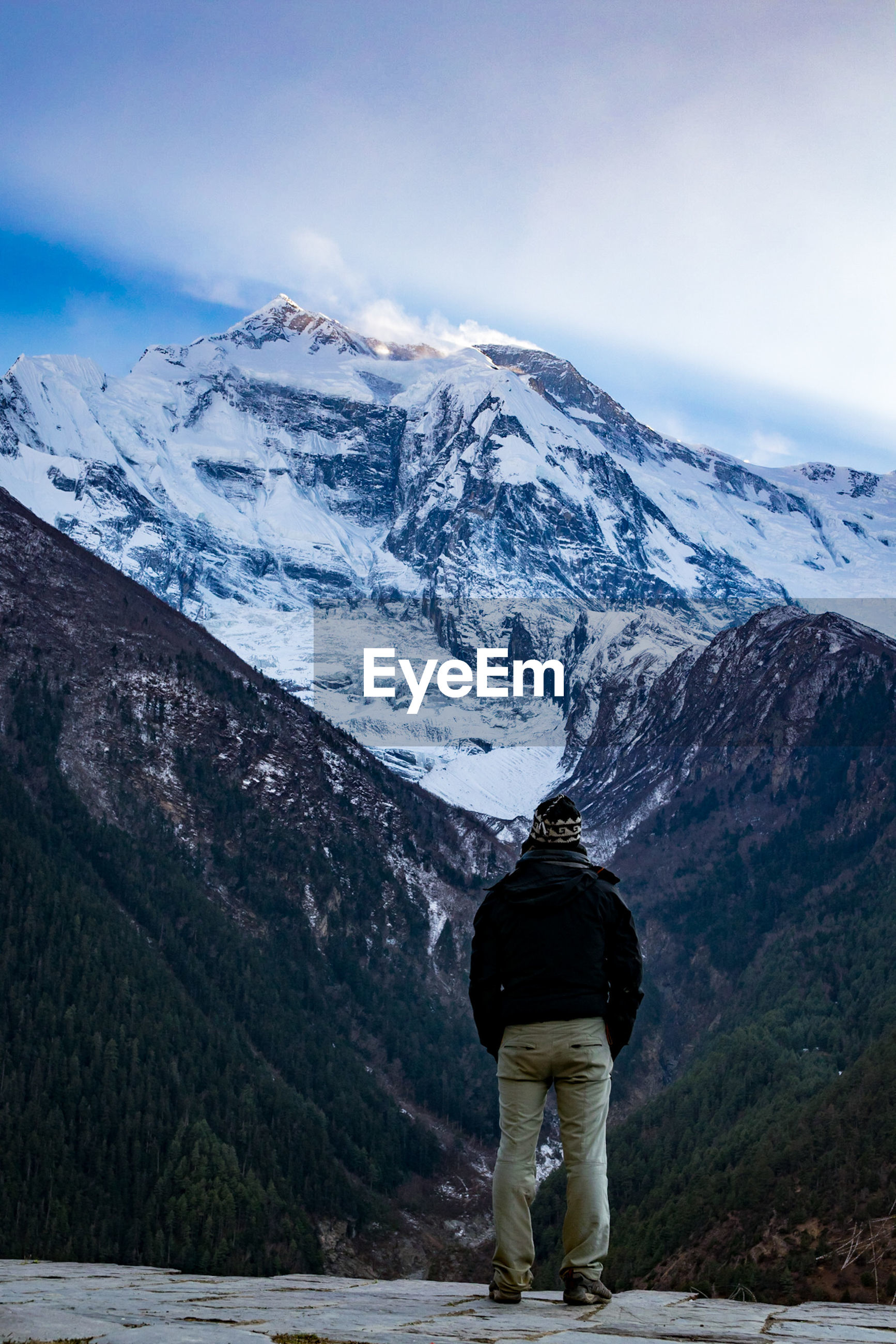 Rear view of man standing against snowcapped mountains
