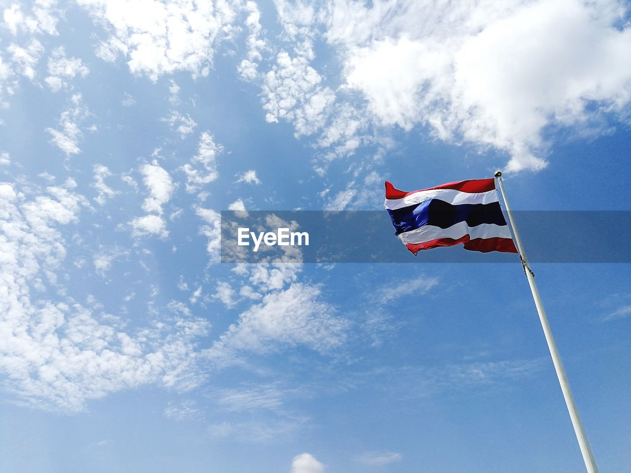cloud - sky, flag, patriotism, sky, low angle view, wind, environment, nature, pole, day, no people, red, white color, waving, outdoors, blue, striped, motion, independence, national icon