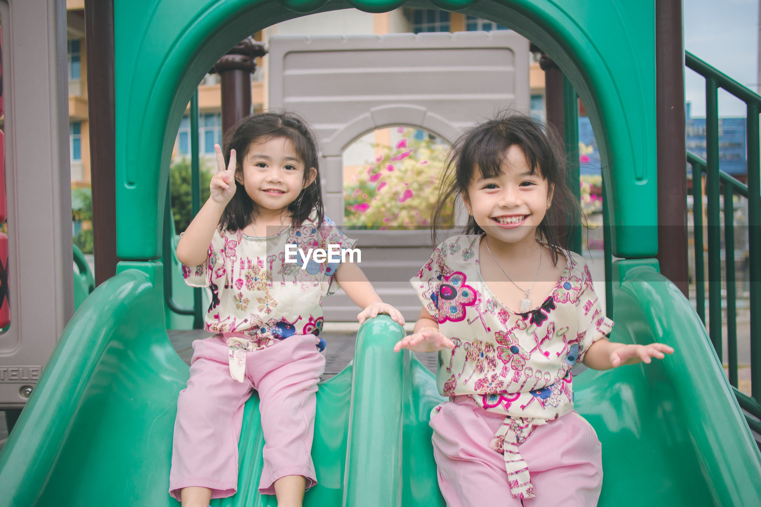 Portrait of cute smiling sisters sliding in park