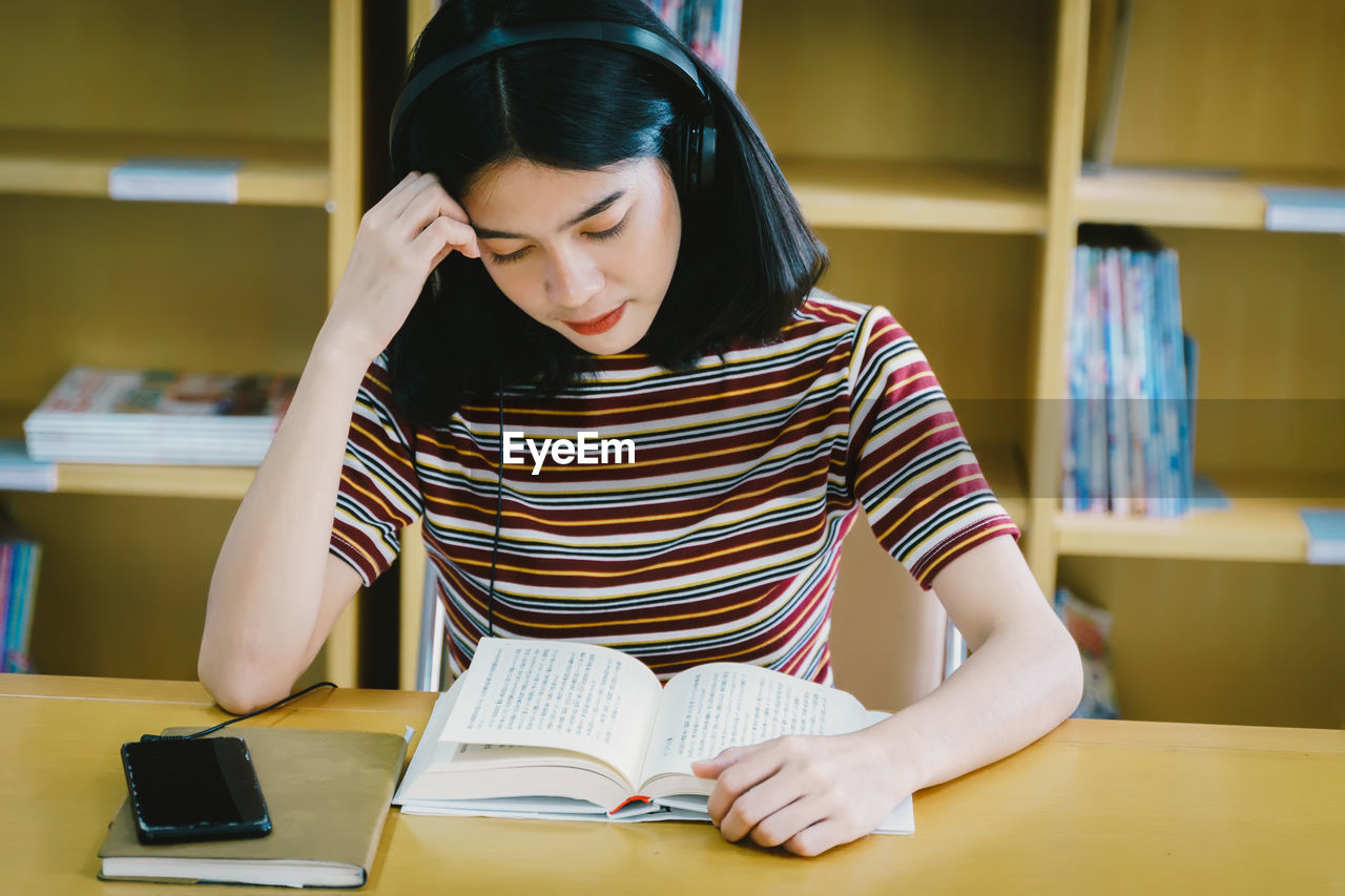 Young woman reading book while listening music on table