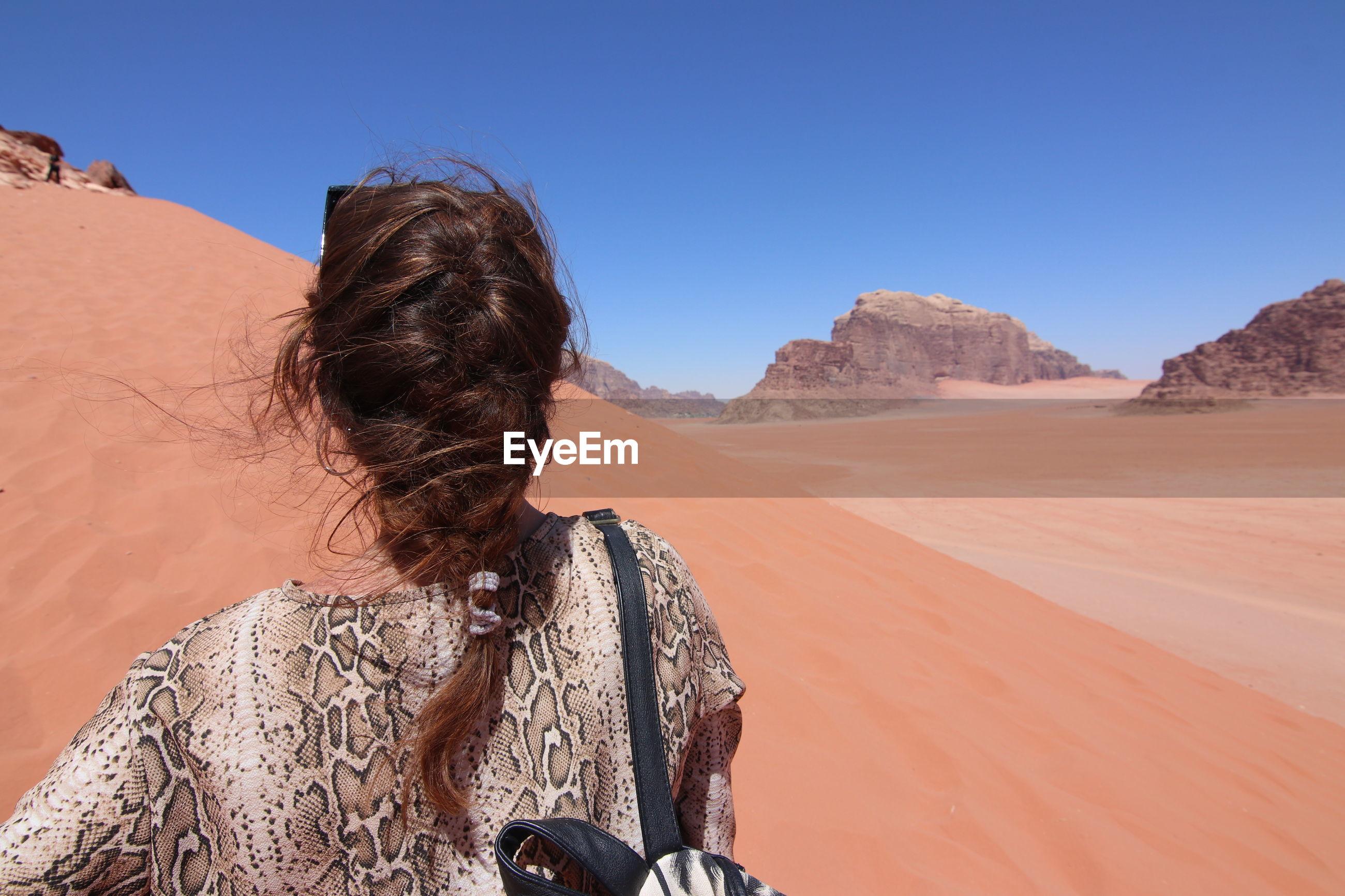 Woman with braided hair walking in the wadi rum desert