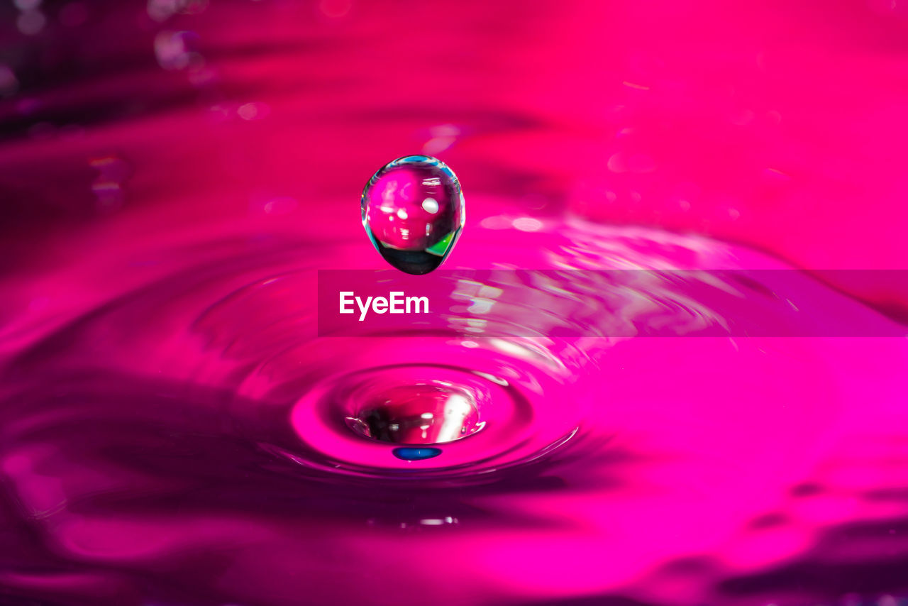 CLOSE-UP OF WATER DROP FALLING ON PINK SURFACE