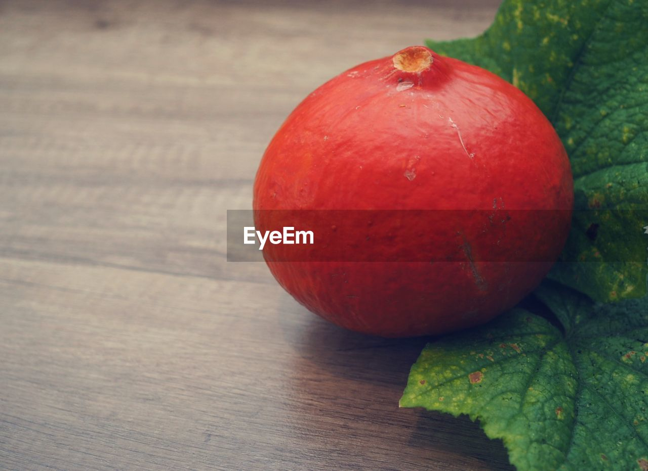 food, healthy eating, food and drink, fruit, wellbeing, freshness, table, close-up, red, still life, no people, wood - material, indoors, focus on foreground, single object, leaf, day, plant part, nature, ripe