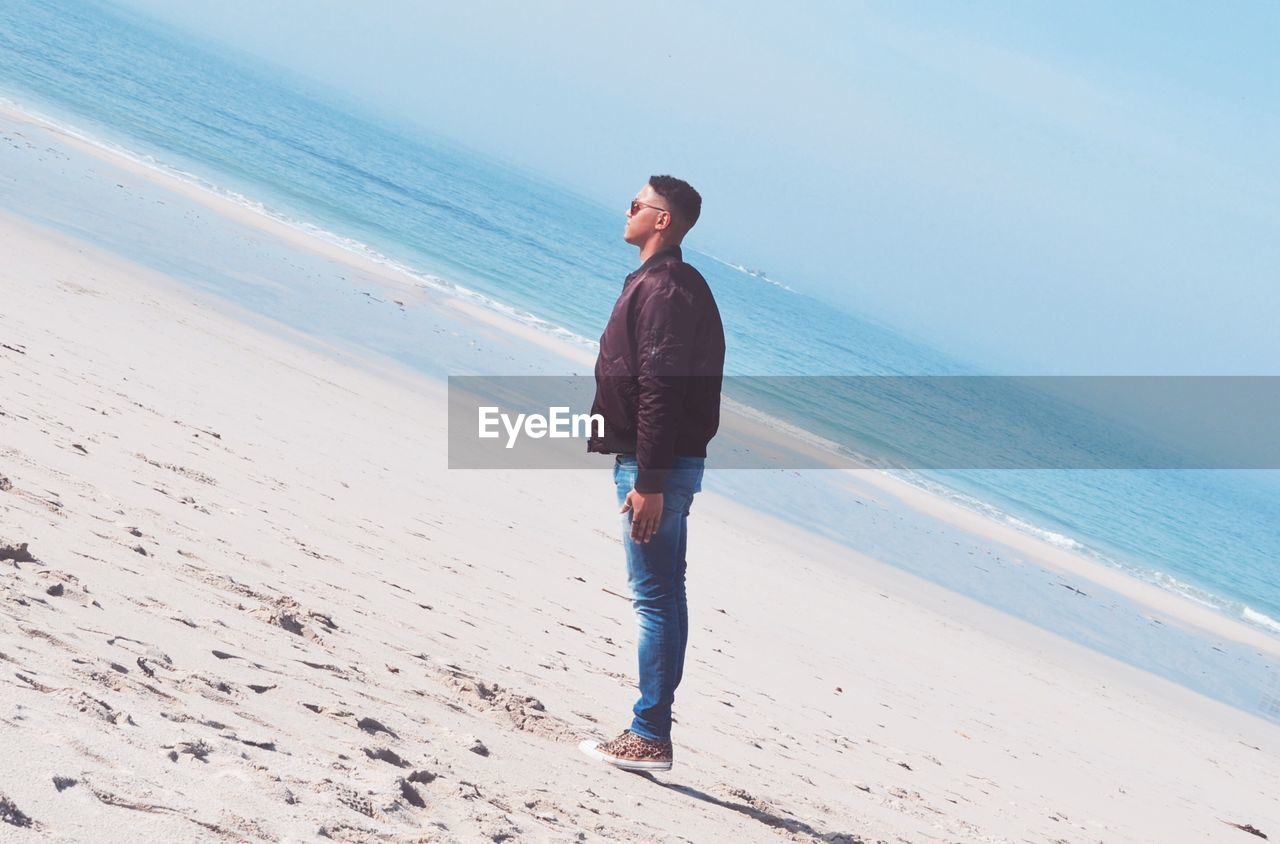 Full length of young man standing on beach