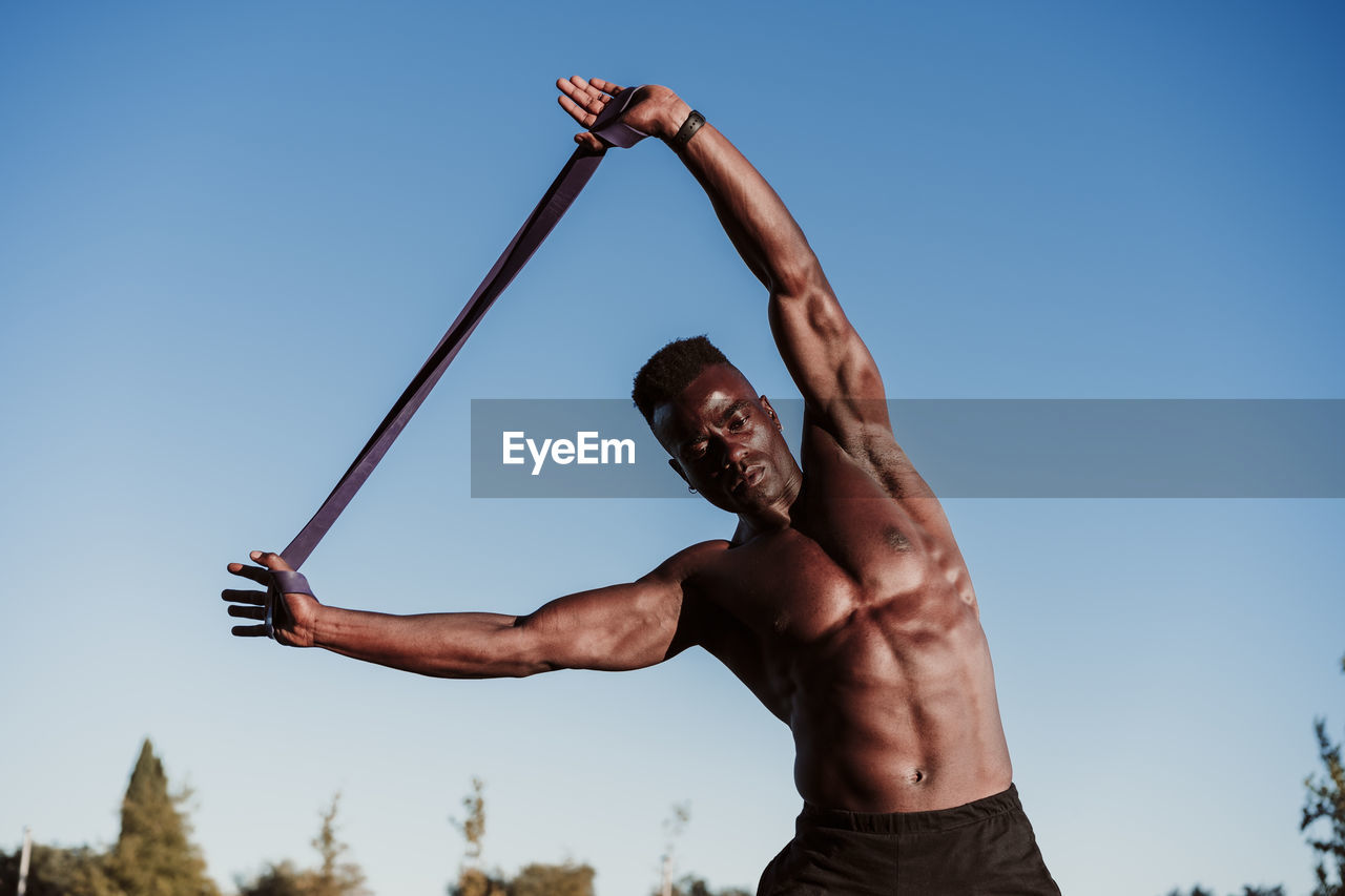 LOW ANGLE VIEW OF SHIRTLESS MAN AGAINST SKY