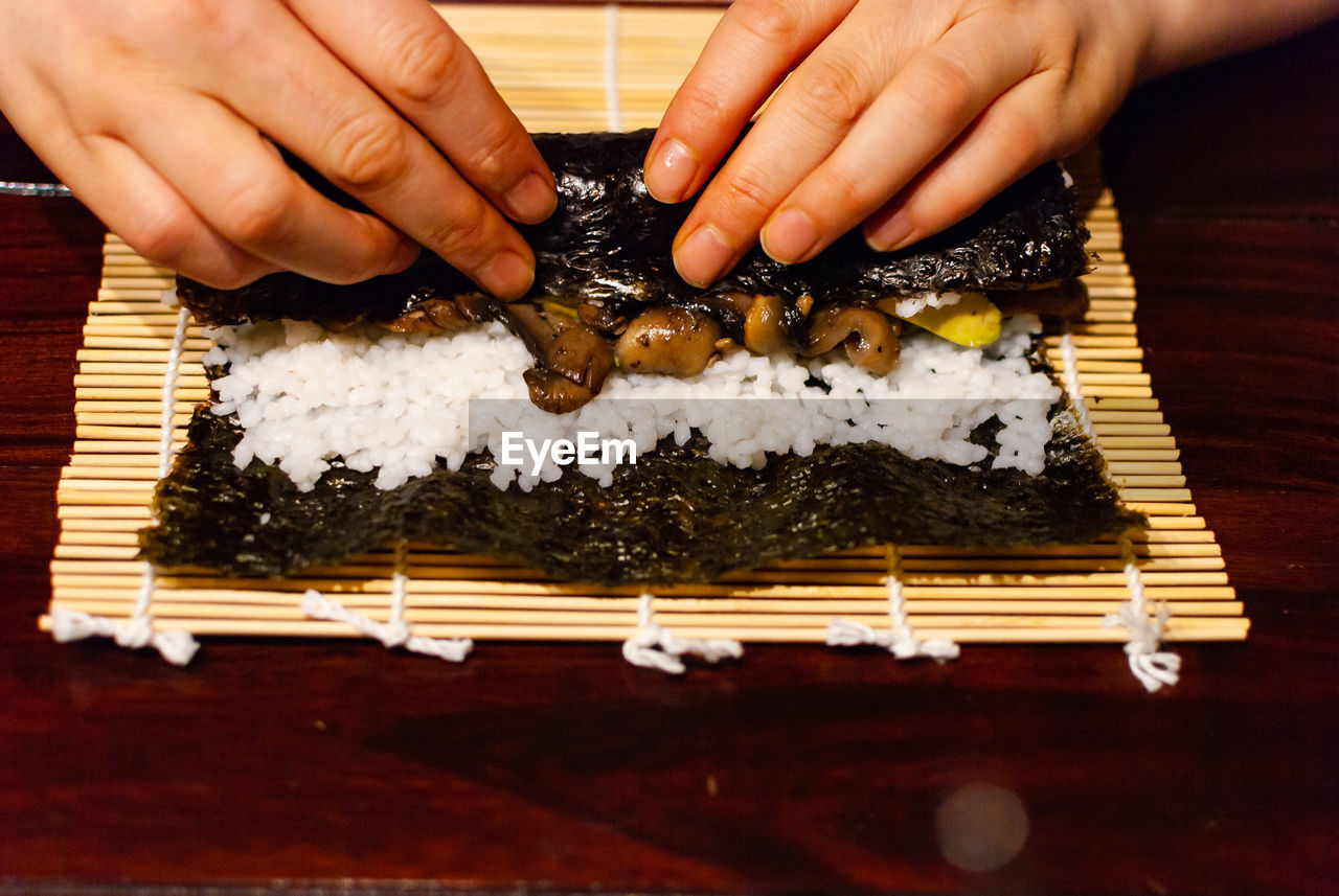human hand, hand, human body part, real people, one person, food, freshness, unrecognizable person, food and drink, indoors, holding, seafood, japanese food, finger, human finger, preparation, rice, asian food, sushi, preparing food