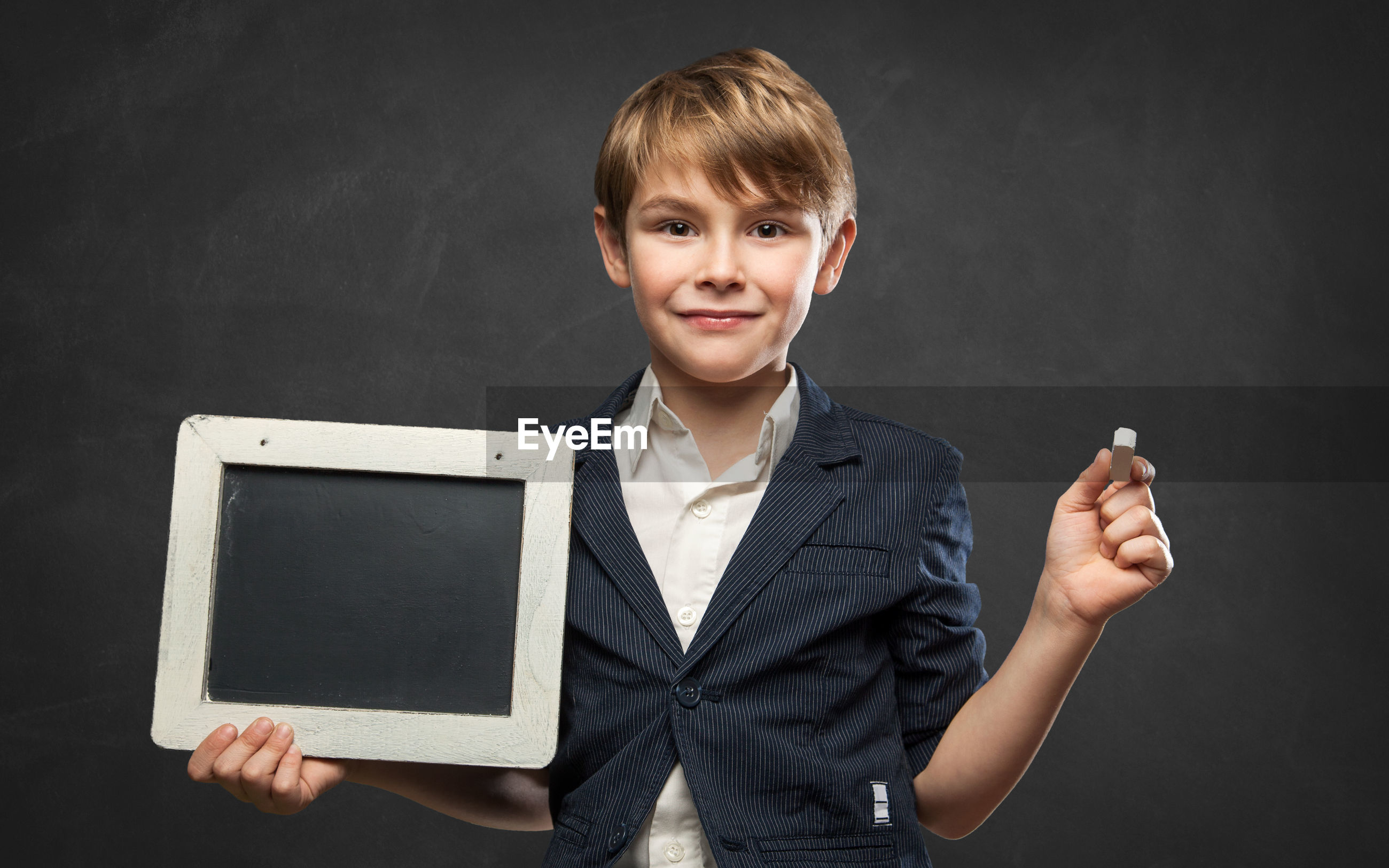 Portrait of boy holding slate standing against black background
