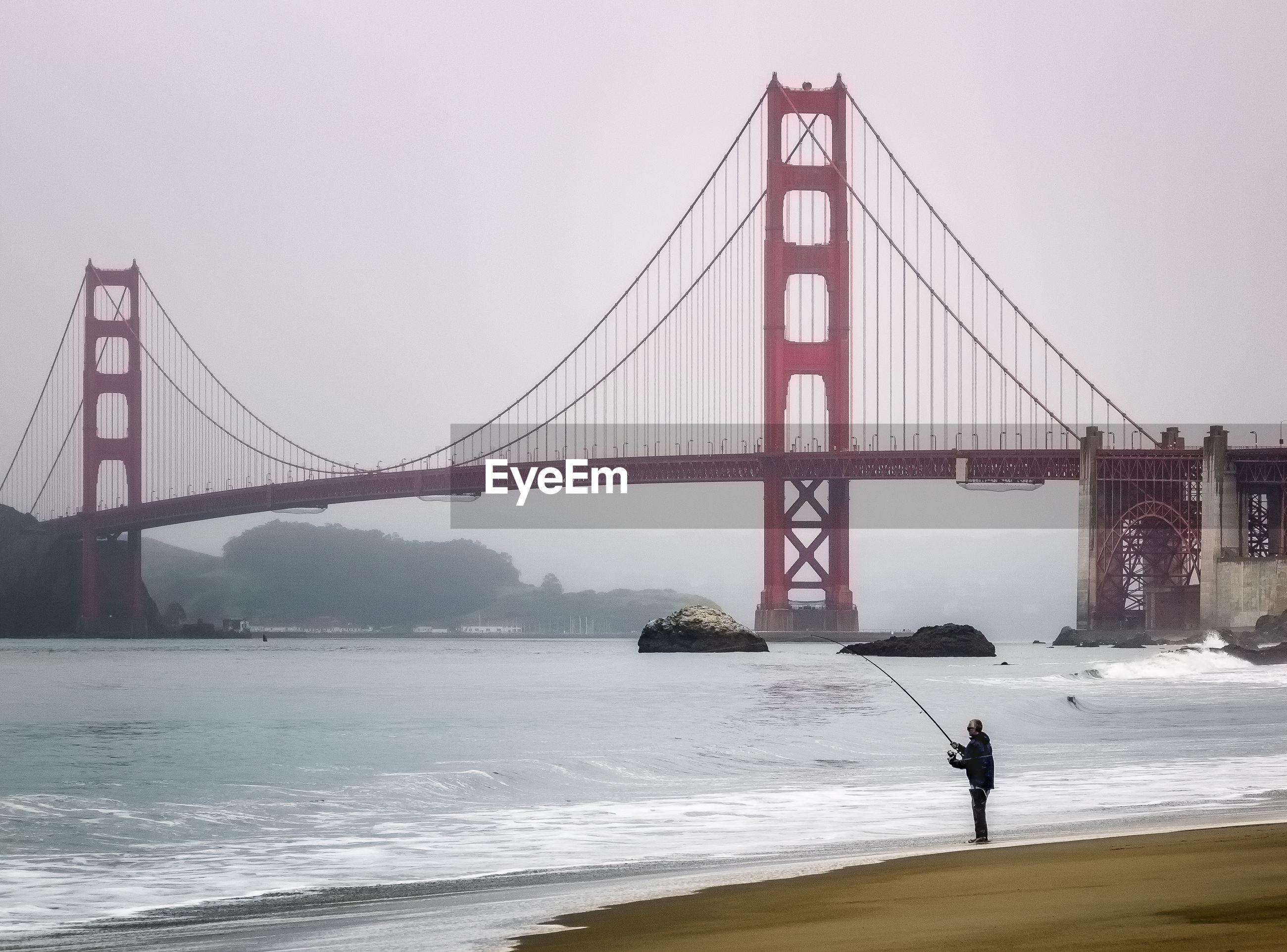 Man with fishing rod standing against golden gate bridge