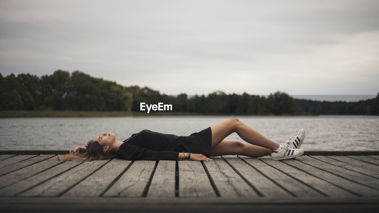 WOMAN LYING ON PIER AGAINST LAKE