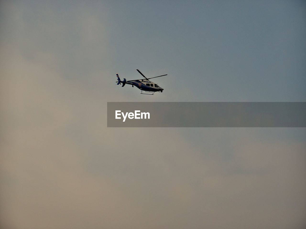 Low Angle View Of Helicopter Flying Against Sky During Sunset