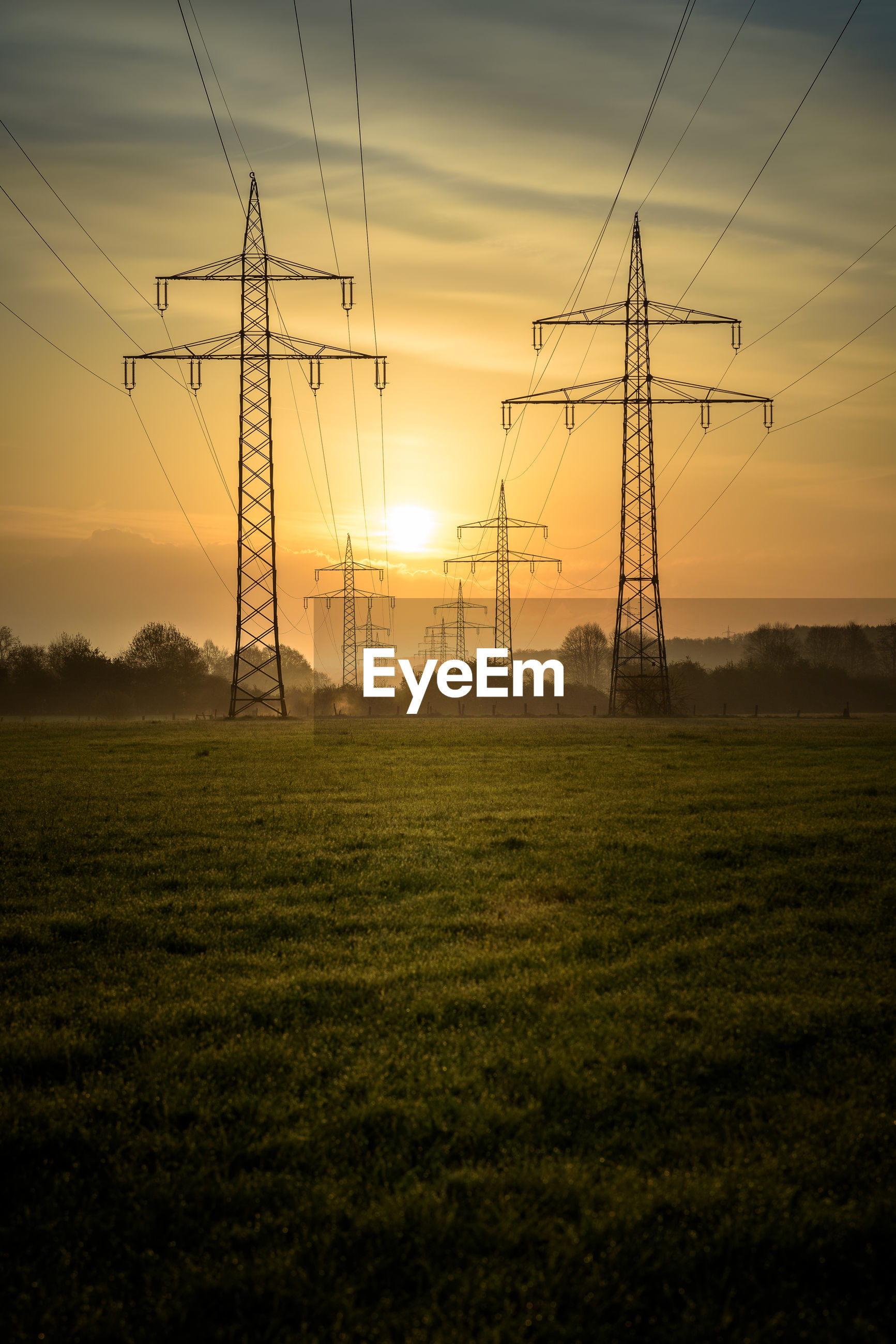 ELECTRICITY PYLONS ON FIELD AGAINST SKY DURING SUNSET