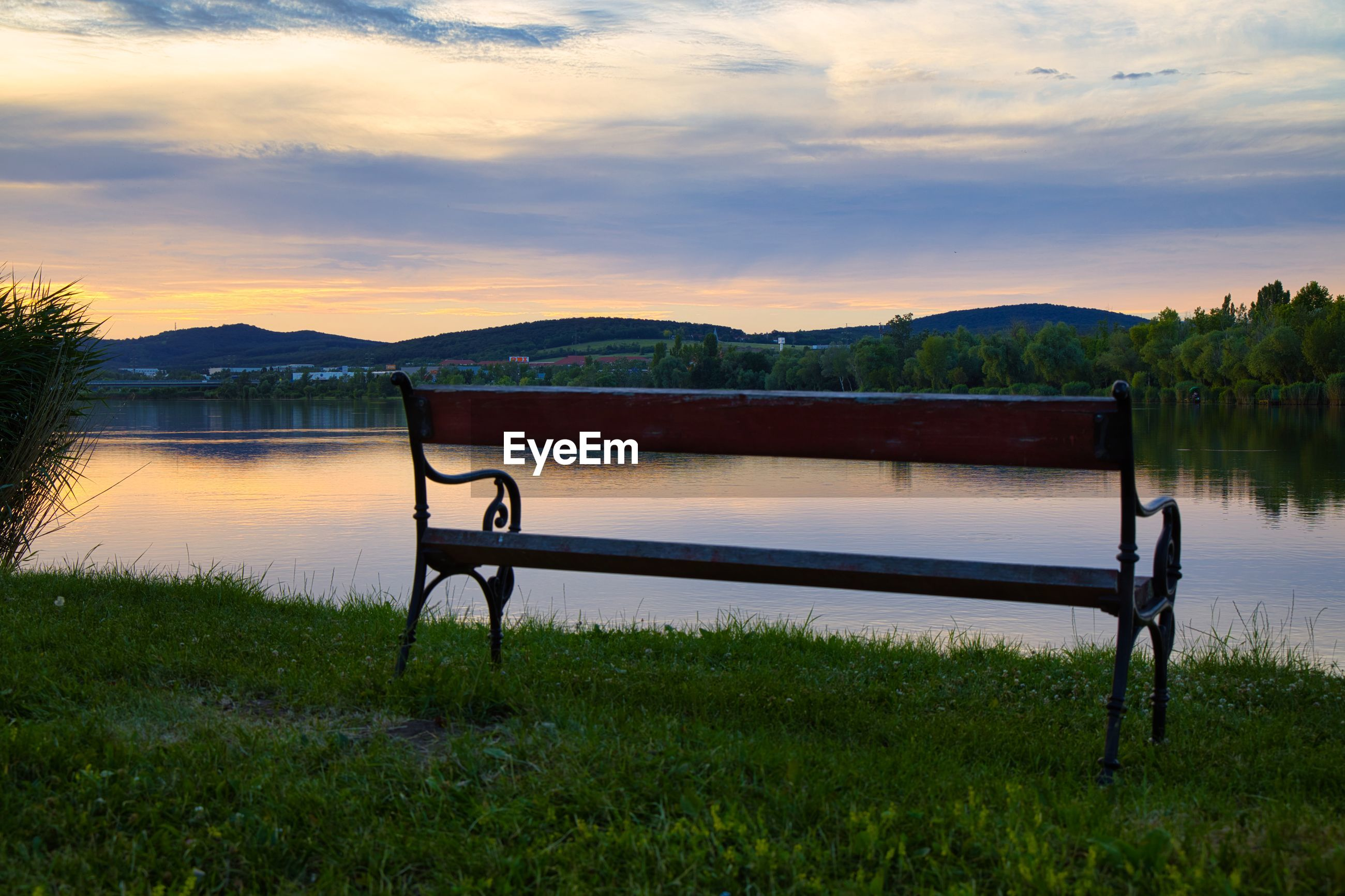BENCH IN LAKE AGAINST SKY DURING SUNSET