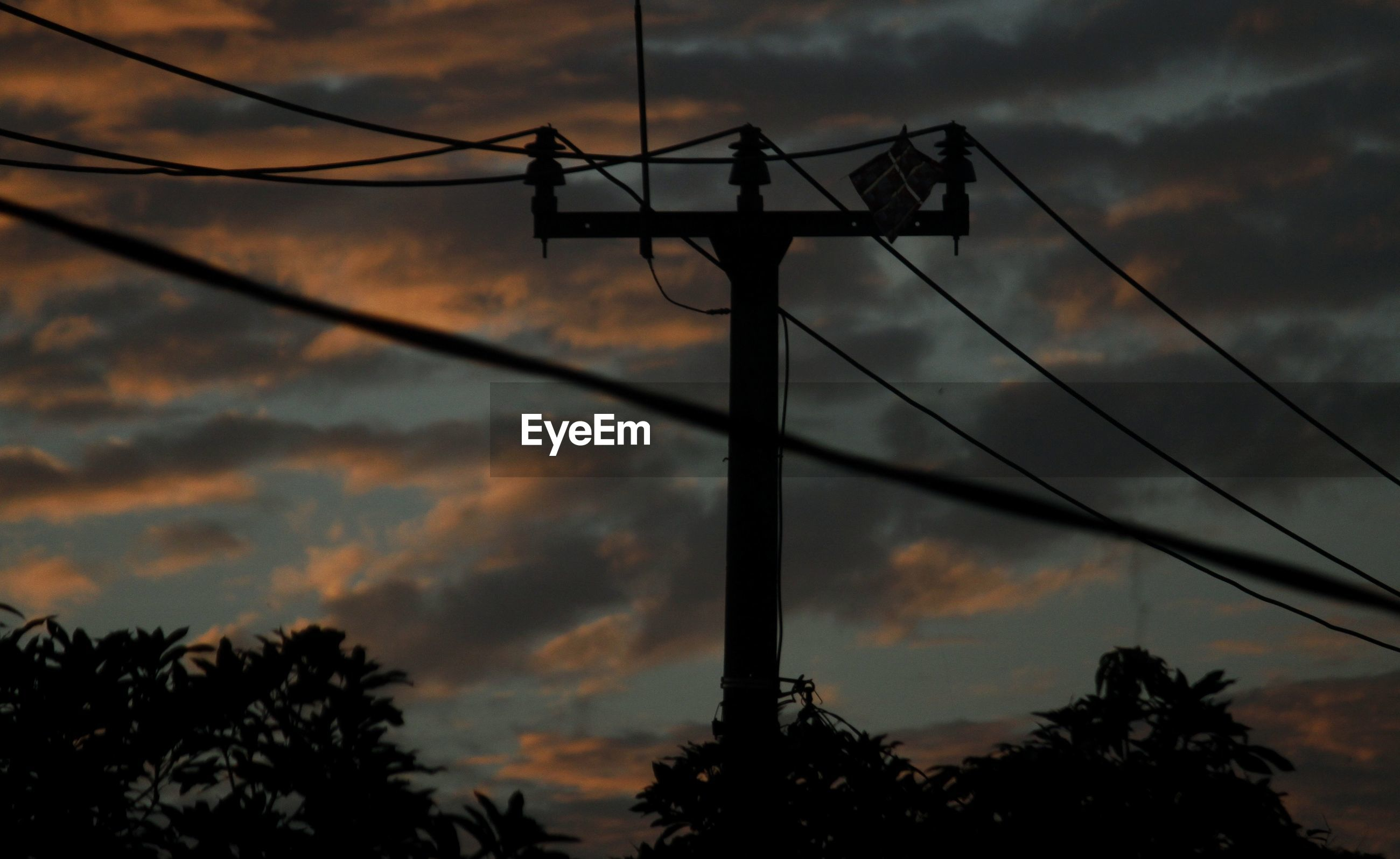 Low angle view of silhouette electric tower against sky at sunset