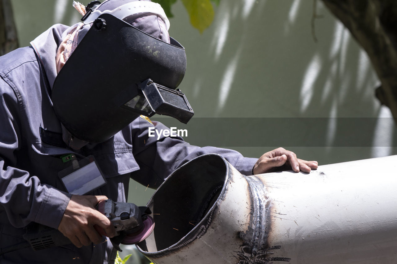 Close-Up Of Man Cutting Pipe