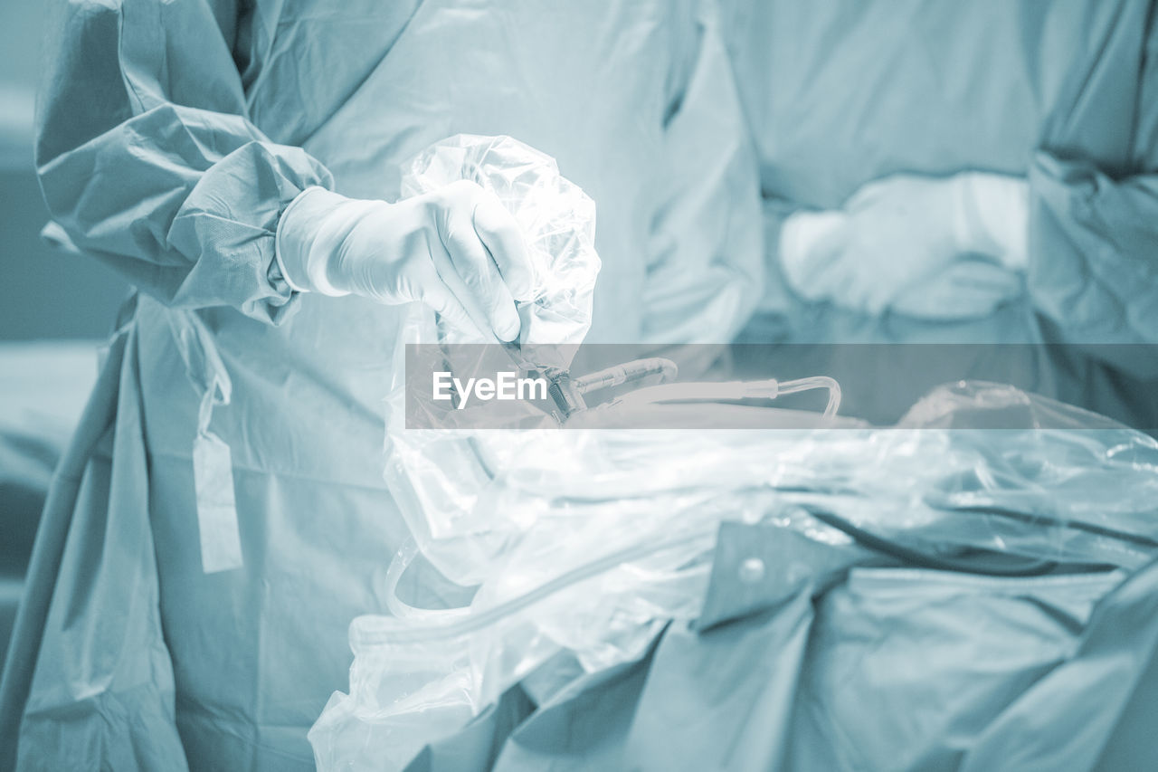 indoors, bed, hospital, linen, healthcare and medicine, furniture, protection, white color, people, security, sheet, textile, body part, close-up, safety, high angle view, real people, surgical glove, care