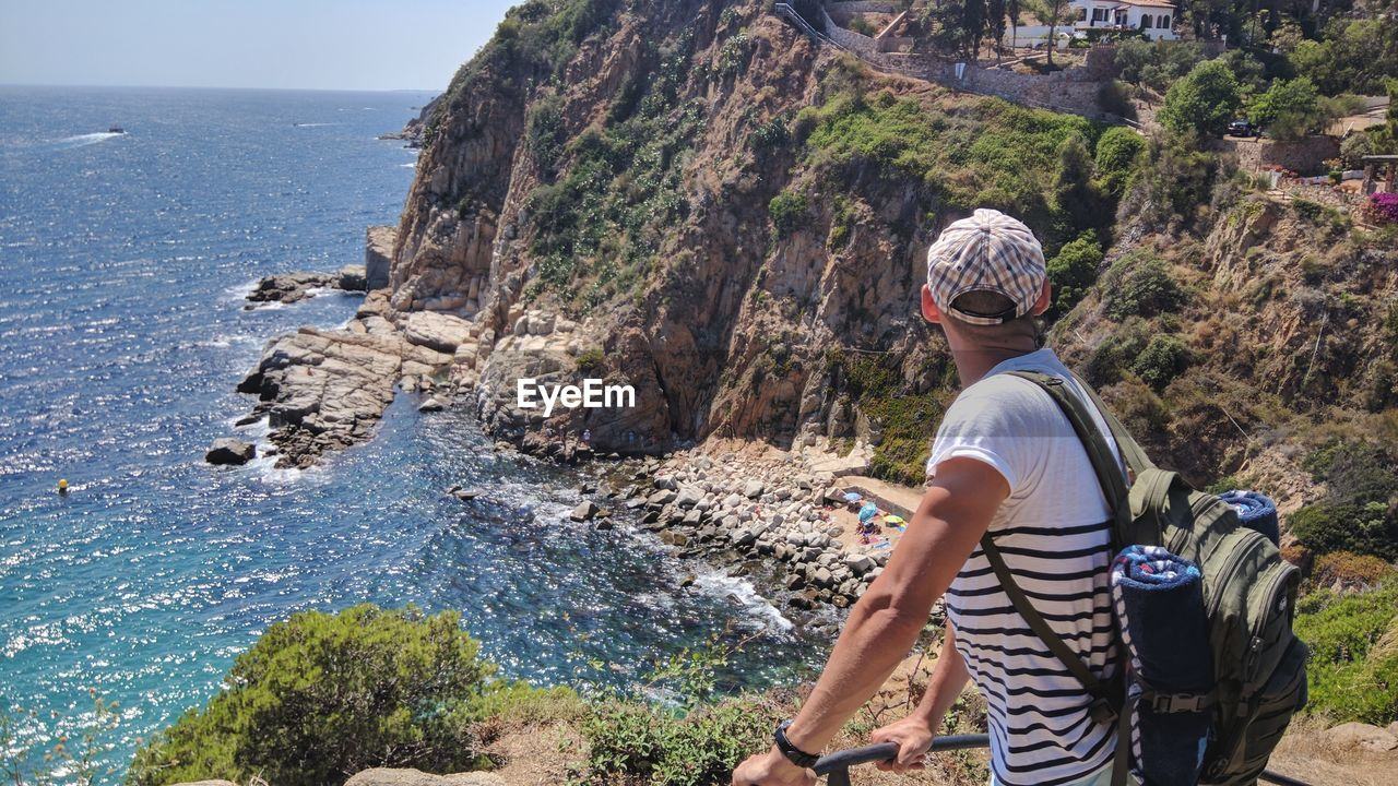 Side View Of Man With Backpack Standing On Rock By Sea