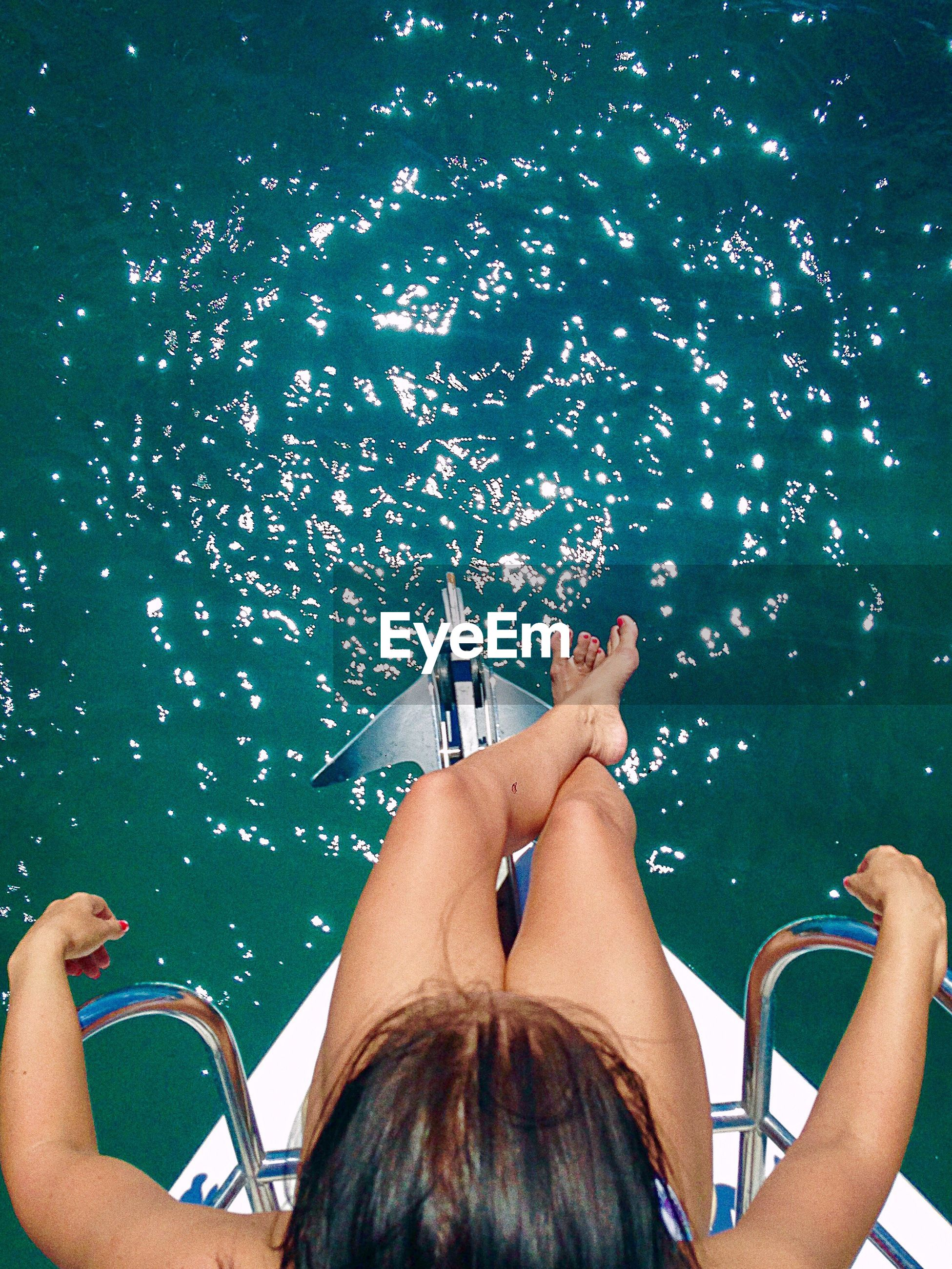 Directly above shot of woman sitting on boat deck sailing in sea