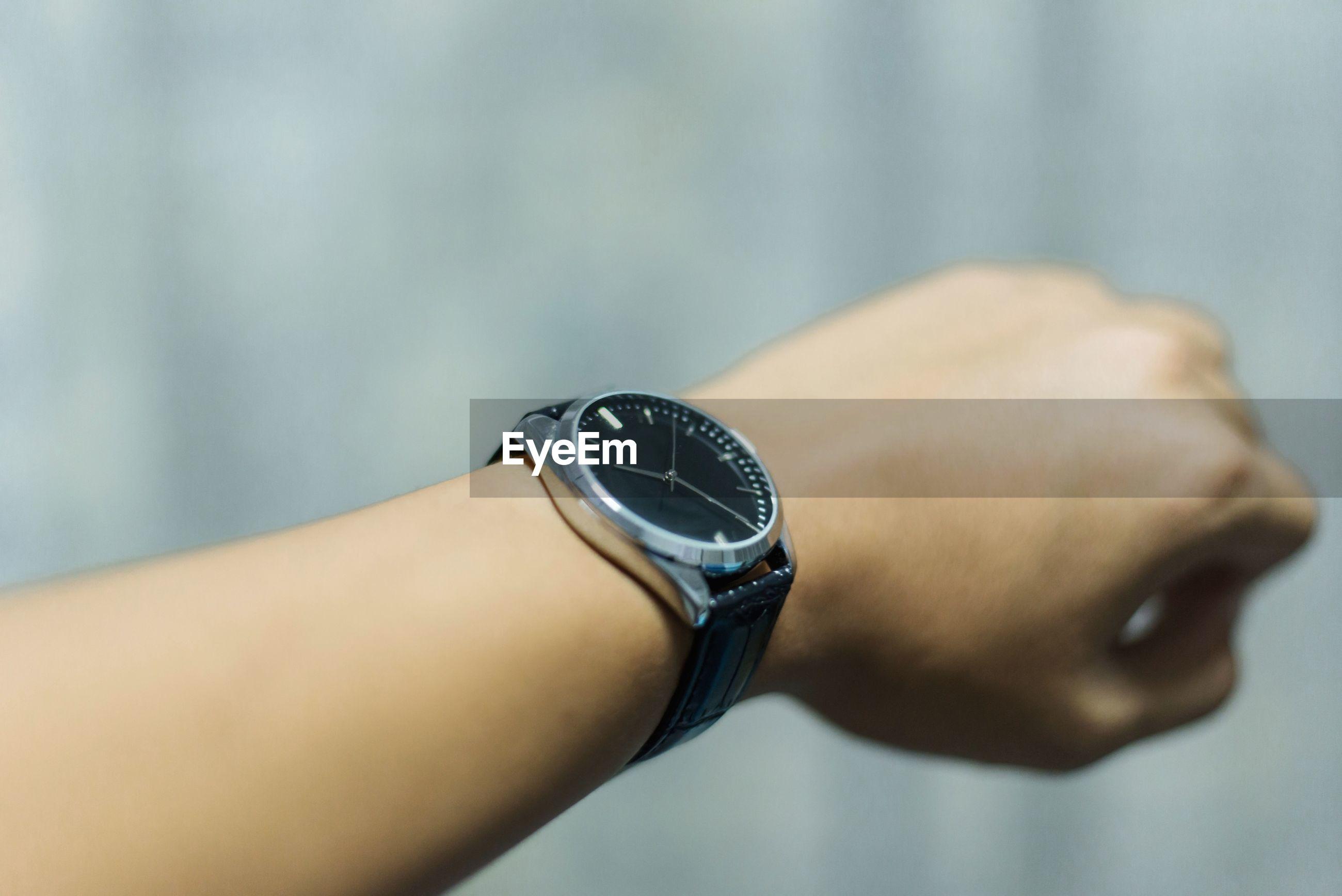 Cropped hand wearing wristwatch