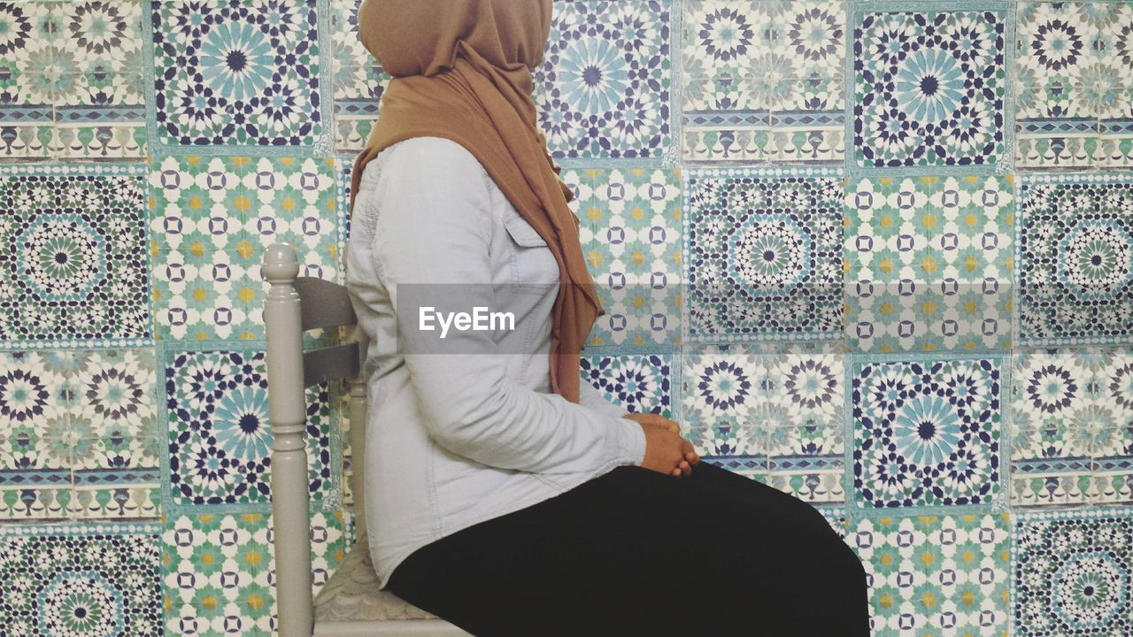 Low section of woman sitting against tiled wall
