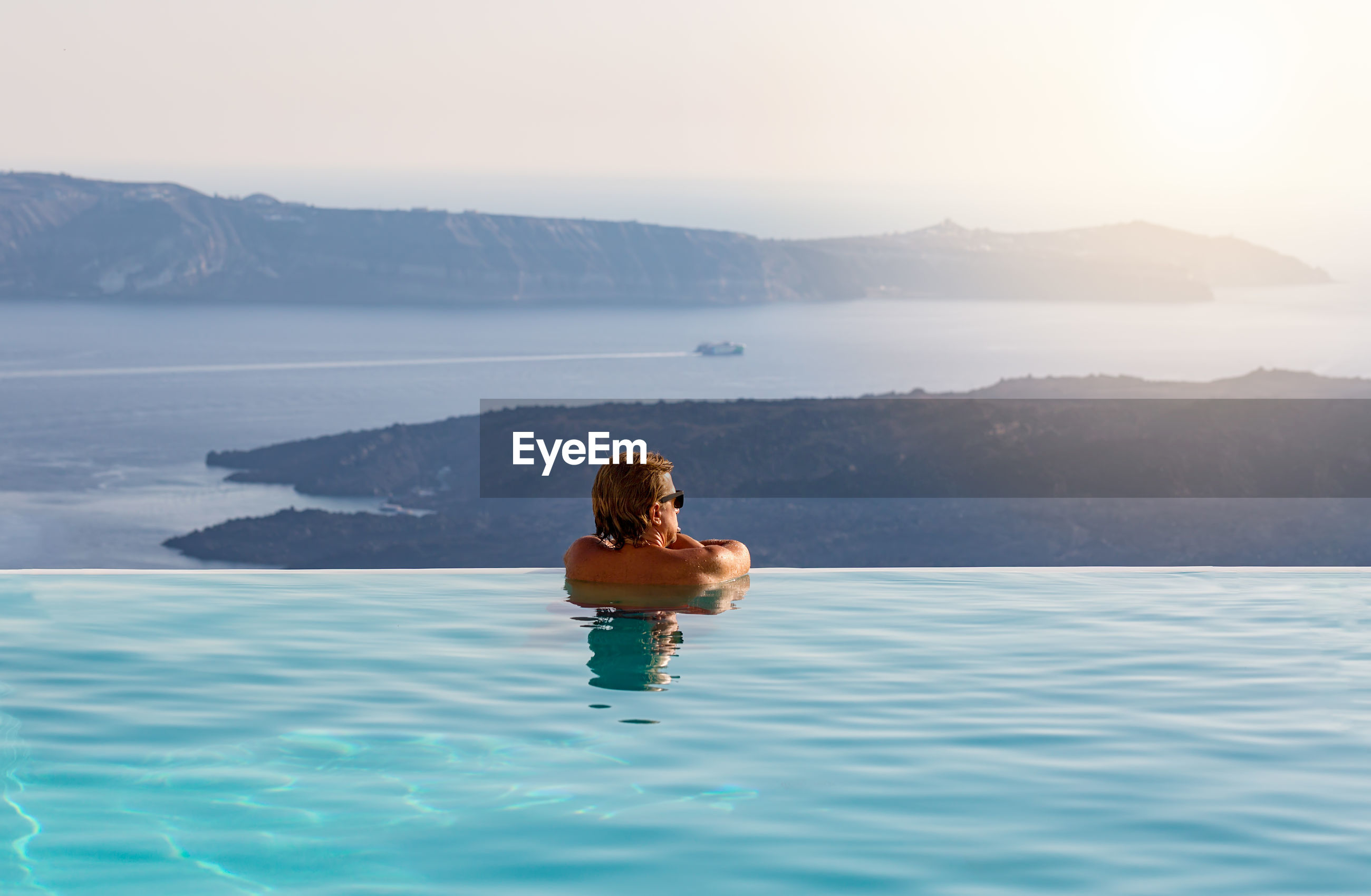 Rear view of shirtless man in infinity pool