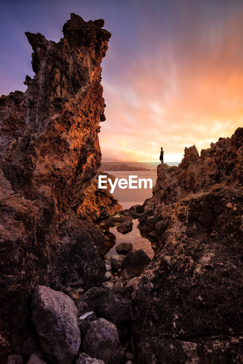 Man Standing On Rock Formation Against Sky During Sunset