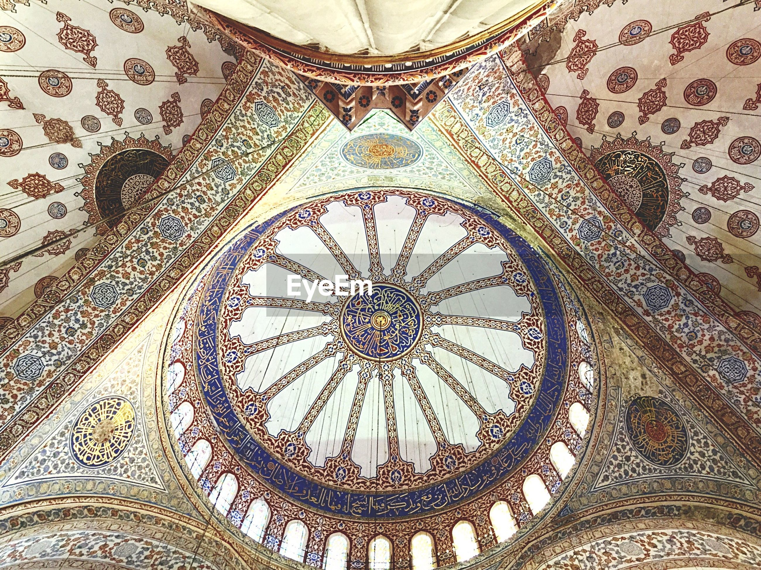 Symmetrical view of ornate mosque ceiling