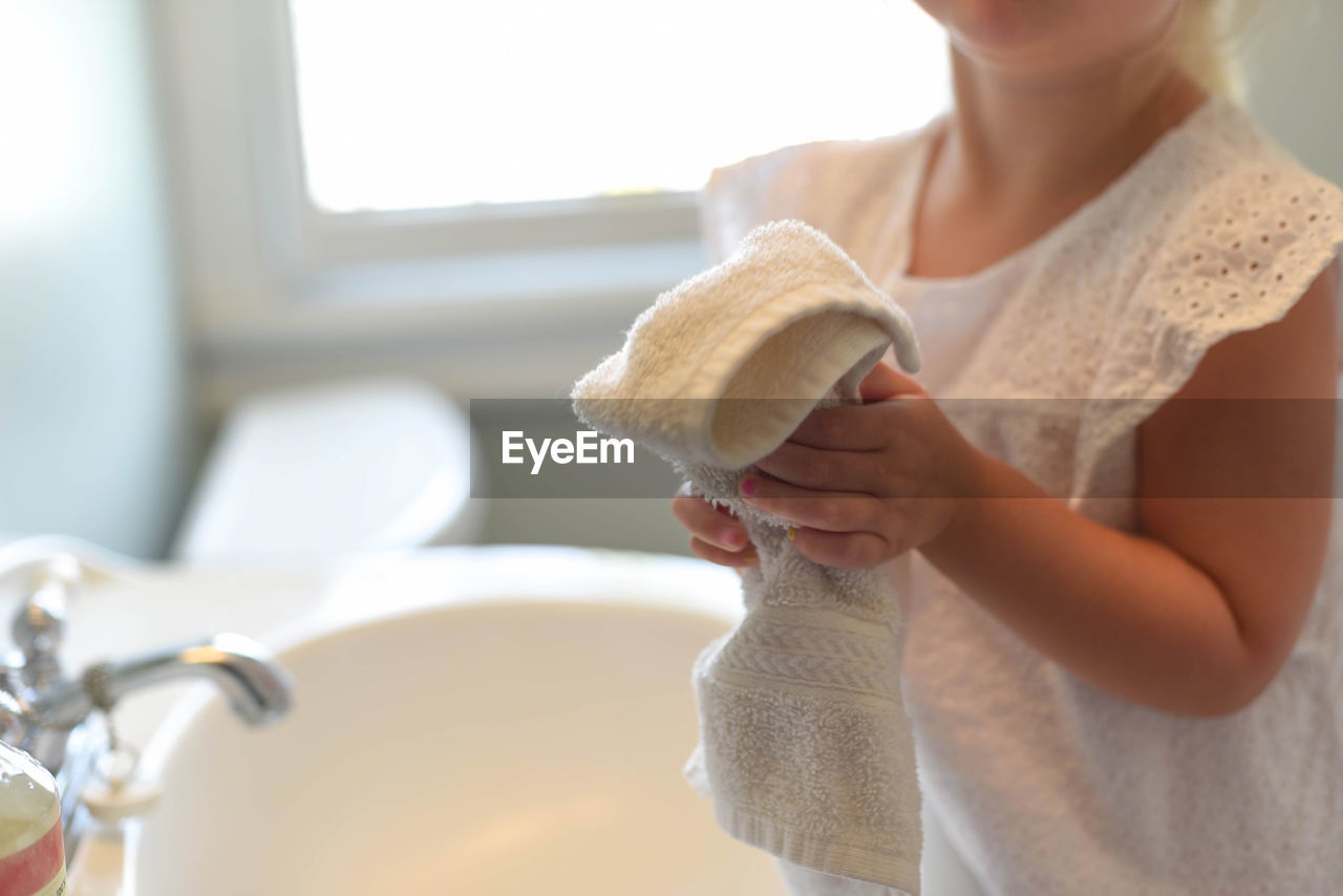 Midsection of girl holding towel at home
