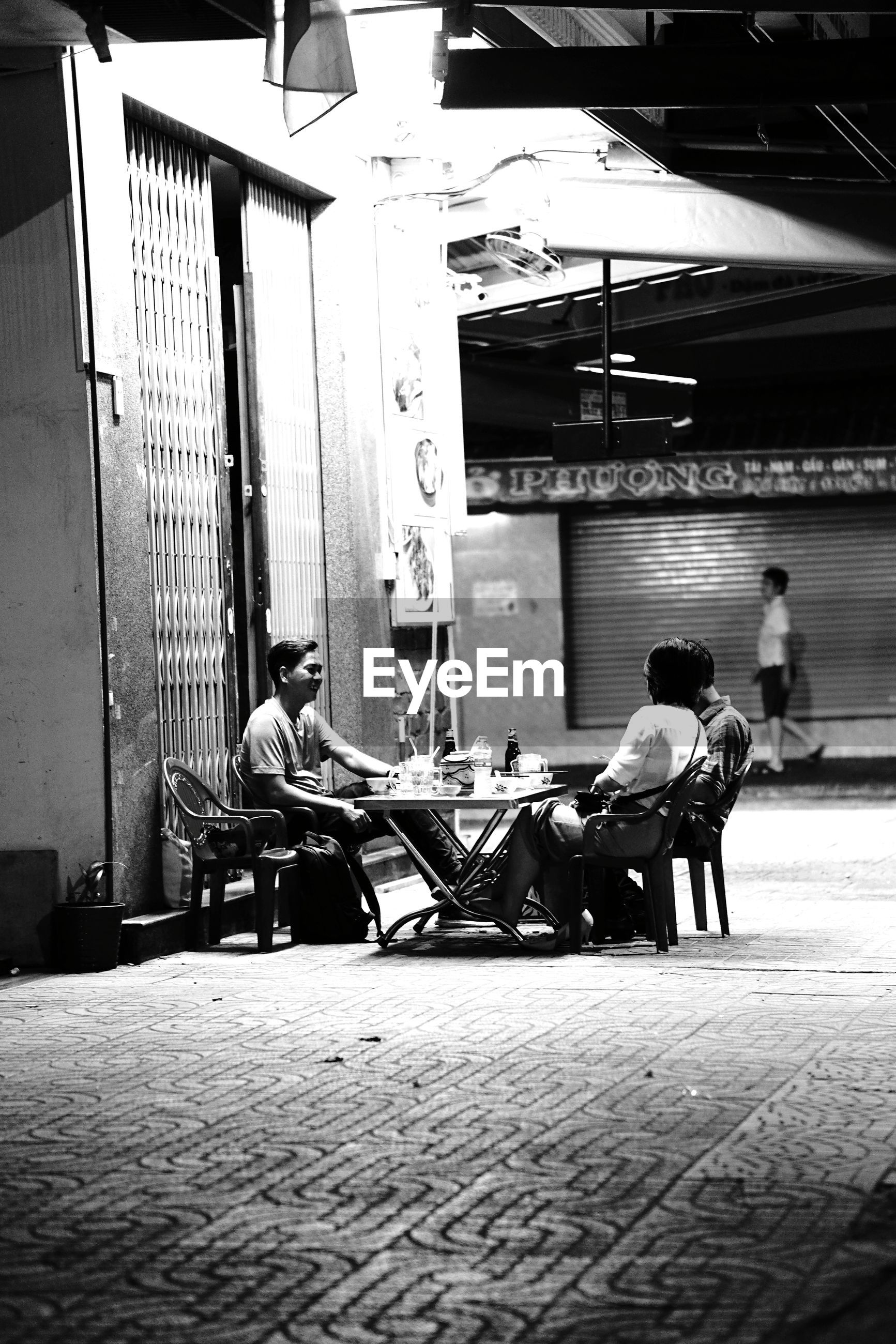 MEN SITTING ON FOOTPATH IN CITY
