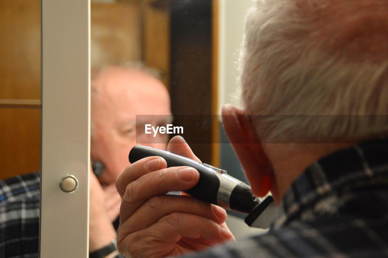 Senior man shaving his face in bathroom