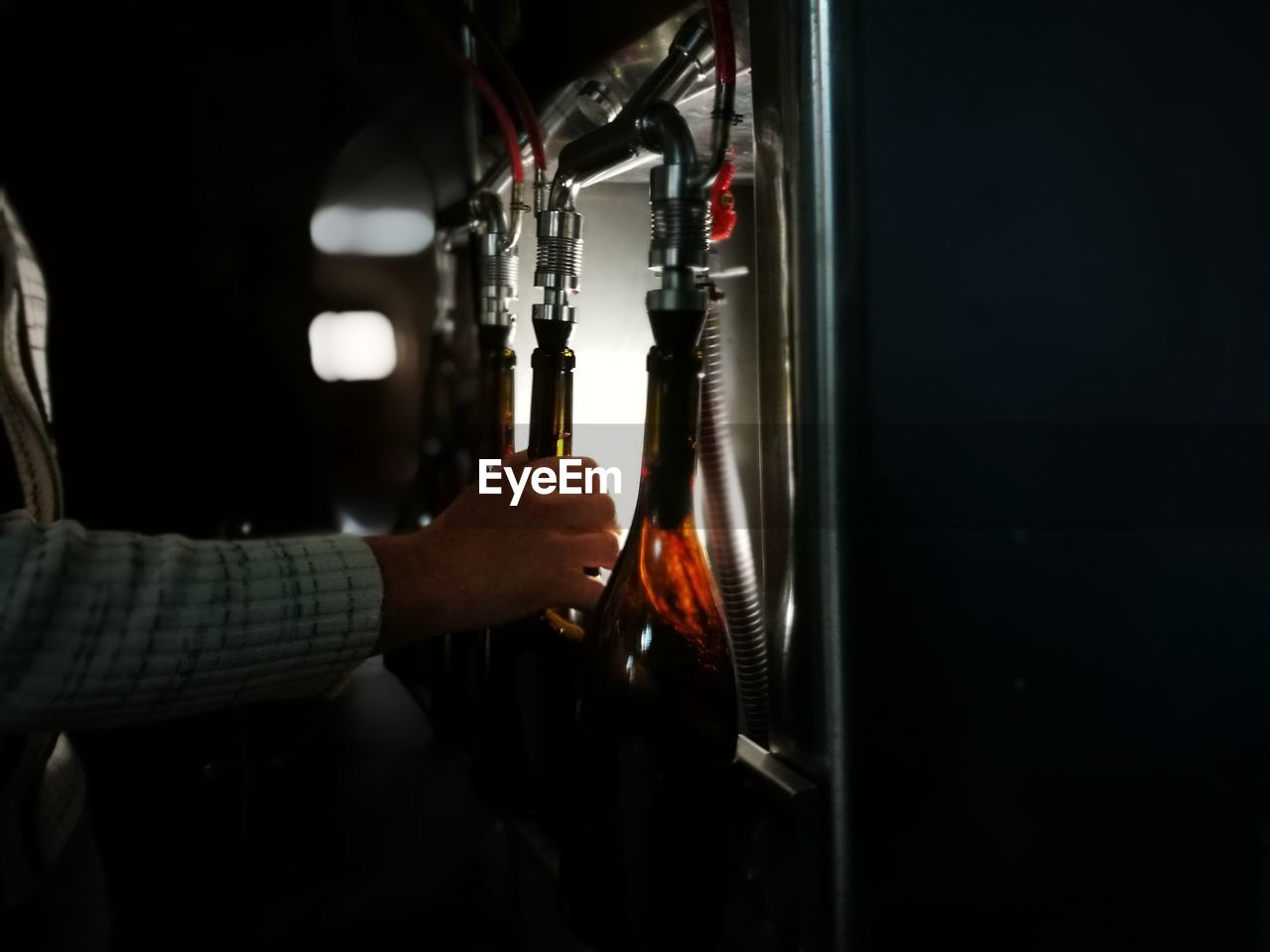 Cropped image person filling wine bottles from bottling machine