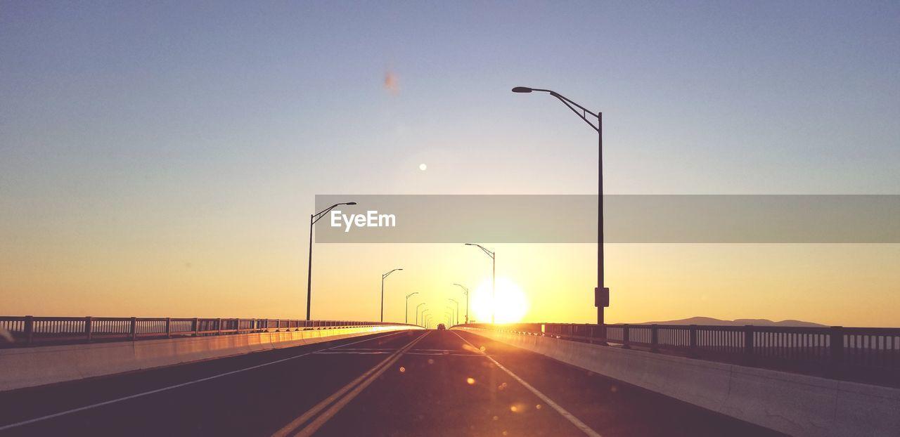 Driving into the sun on a bridge