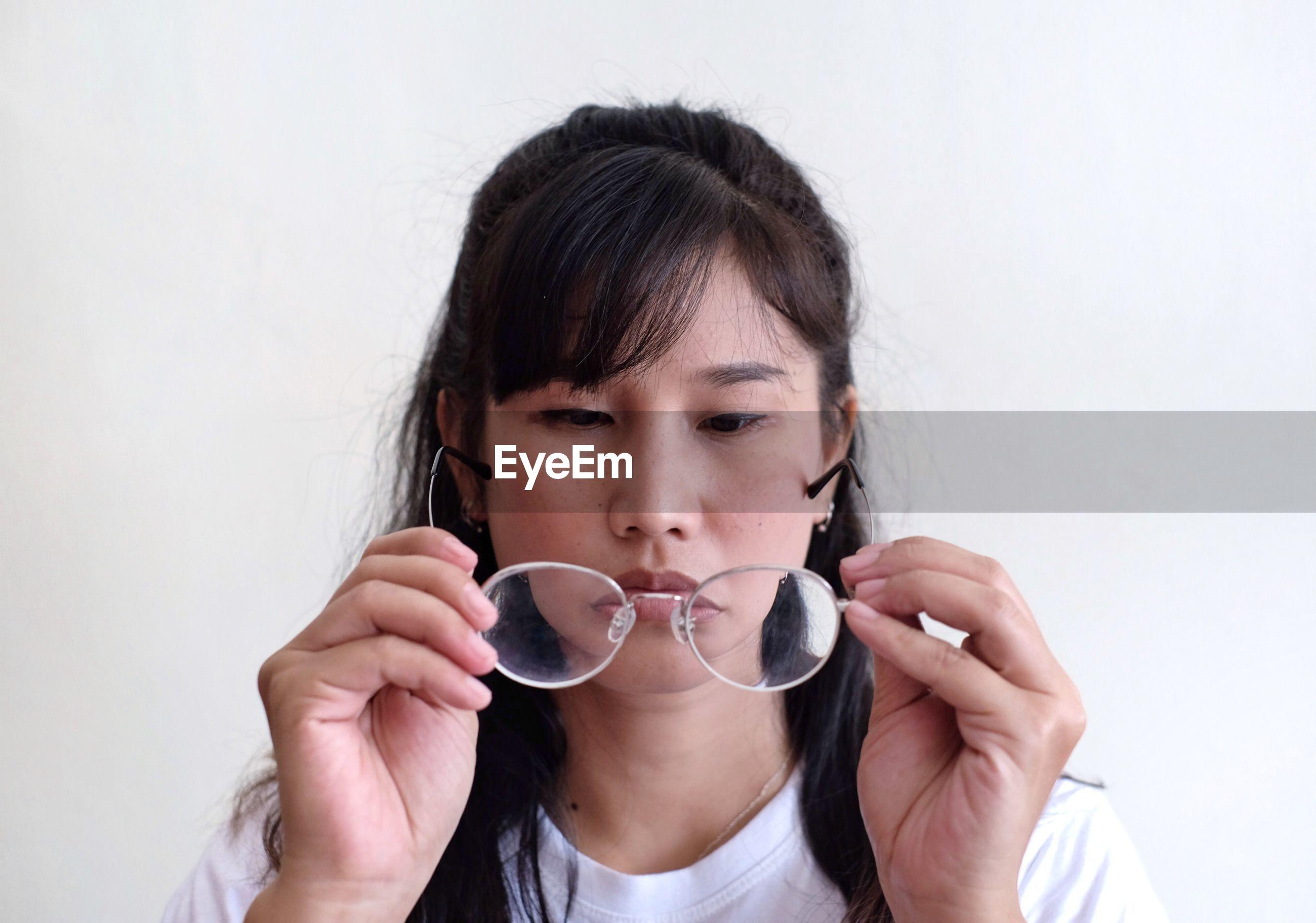Close-up portrait of a women holding glasses