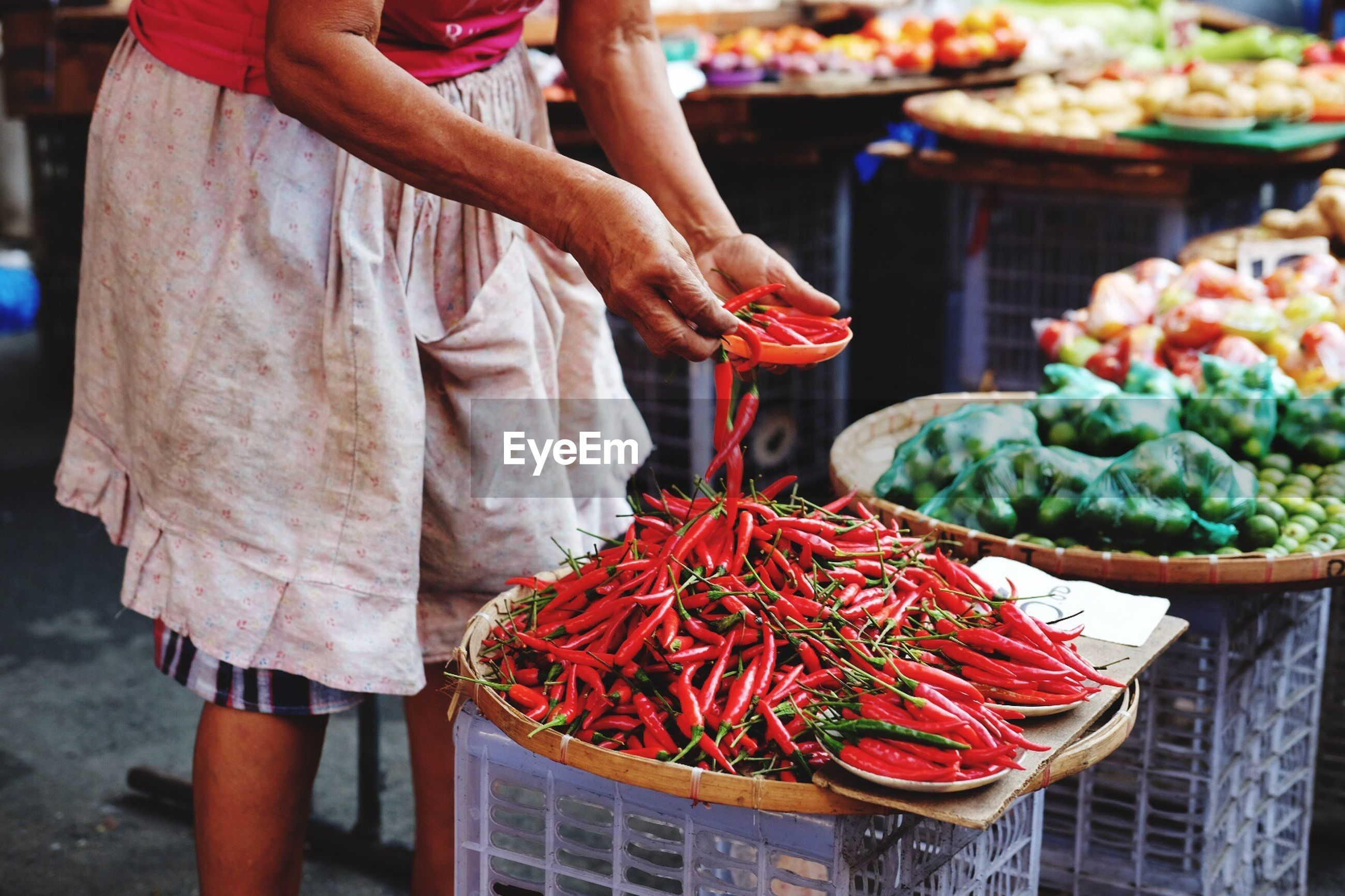 Man holding red chilies at market stall
