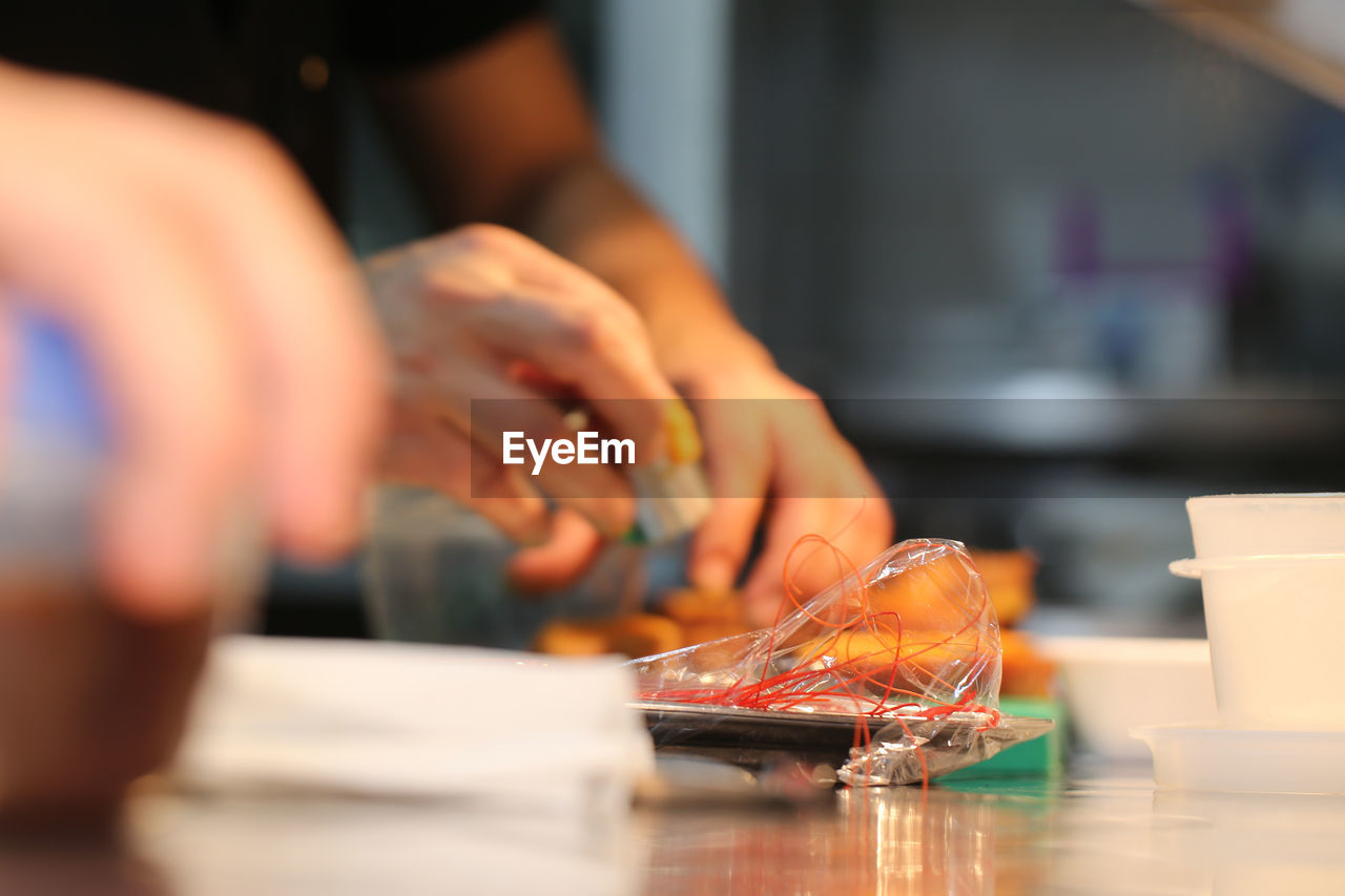 selective focus, real people, hand, indoors, one person, human hand, table, holding, human body part, food and drink, business, food, unrecognizable person, working, freshness, occupation, close-up, seafood, restaurant, finger