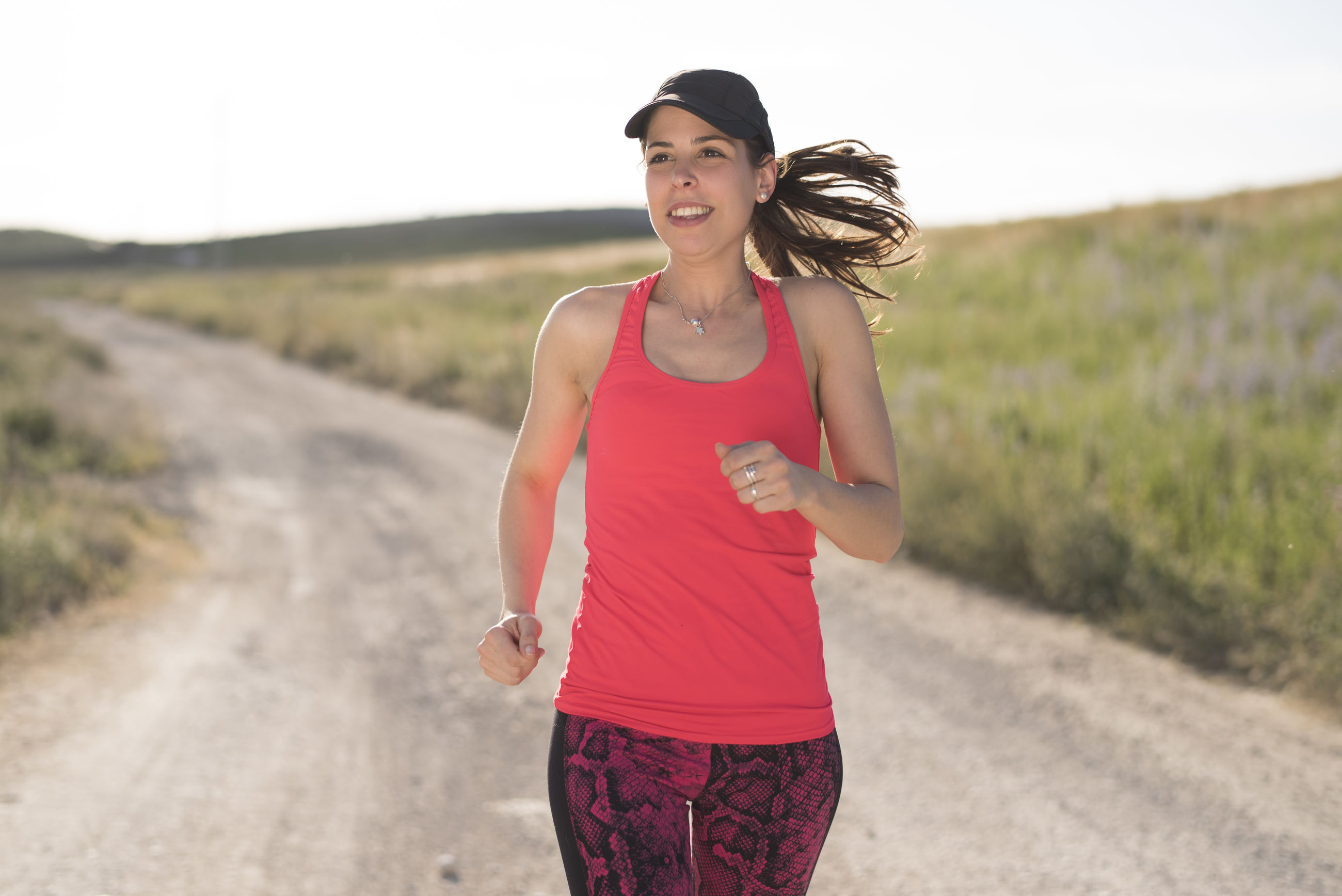 Smiling mid adult woman looking away while jogging on dirt road during sunny day