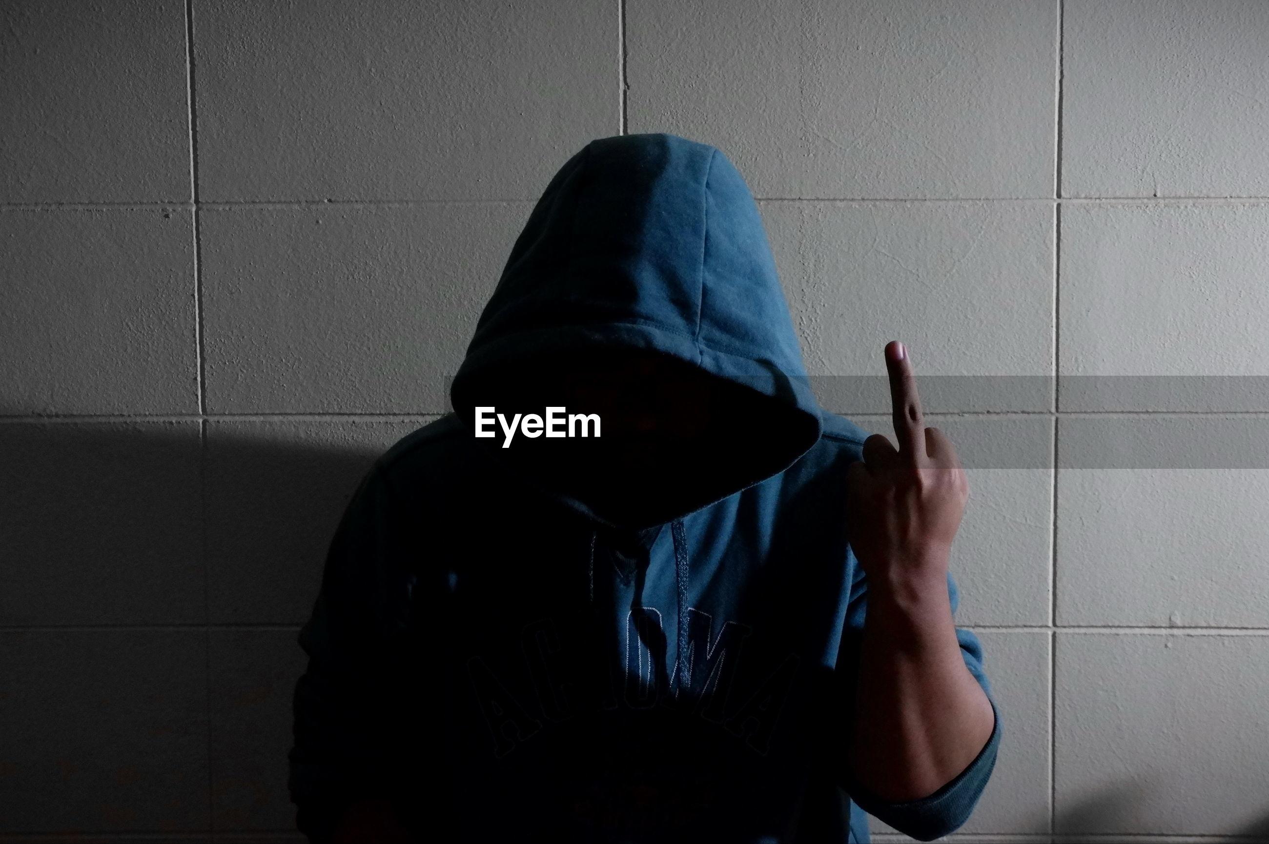 Man wearing hood gesturing standing against wall