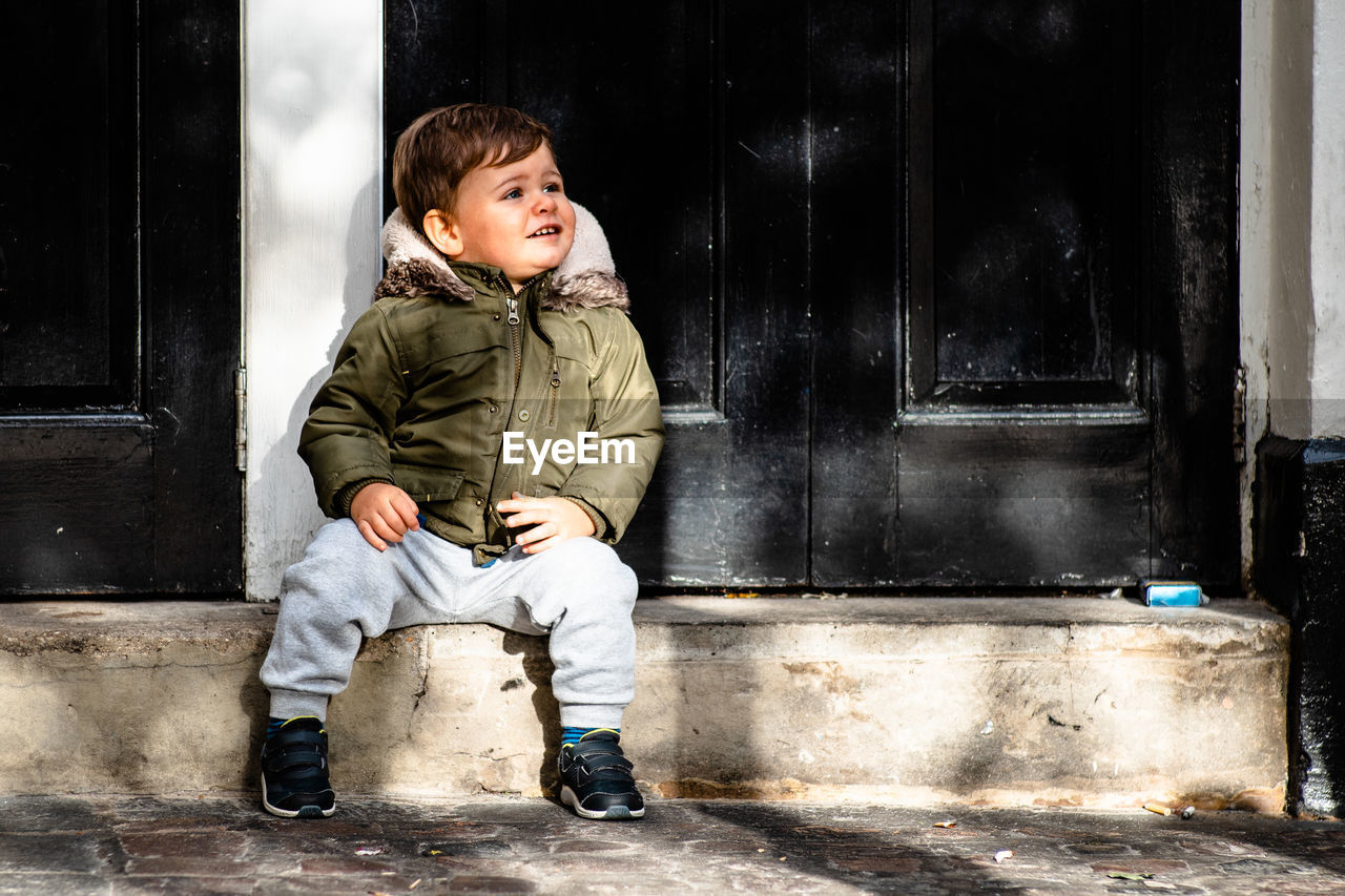 childhood, child, full length, males, boys, real people, men, architecture, entrance, sitting, front view, one person, door, emotion, lifestyles, day, innocence, casual clothing, outdoors, warm clothing