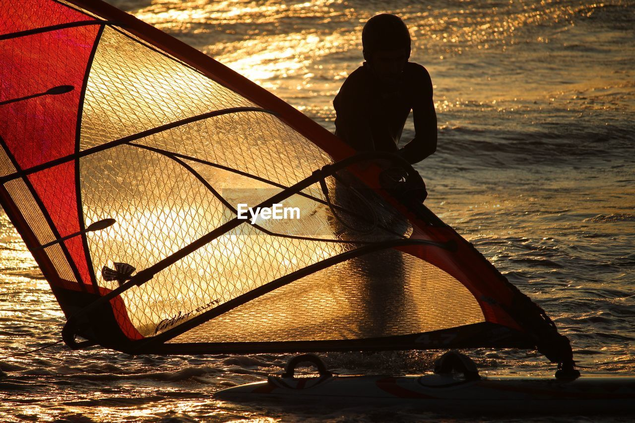 water, sea, real people, sunset, leisure activity, men, lifestyles, nature, beach, nautical vessel, sky, people, land, sunlight, transportation, beauty in nature, silhouette, full length, outdoors