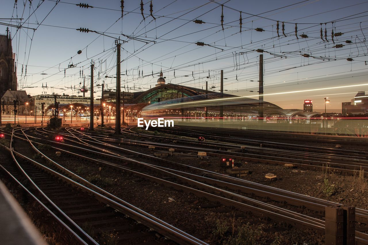 rail transportation, railroad track, track, transportation, mode of transportation, sky, train, public transportation, electricity, motion, cable, train - vehicle, long exposure, illuminated, architecture, nature, no people, travel, blurred motion, speed, power supply, outdoors, complexity