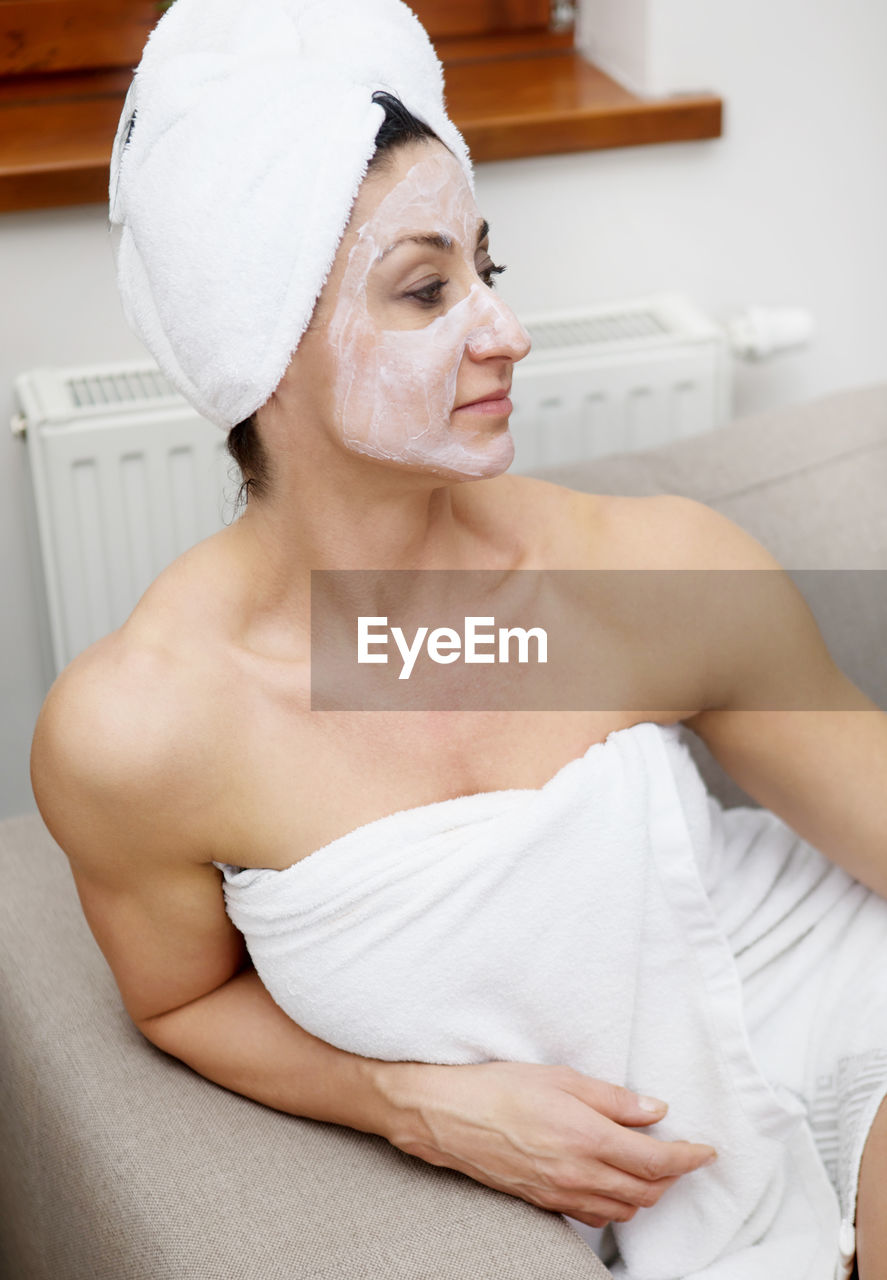 Woman With Face Mask Sitting On Sofa At Home
