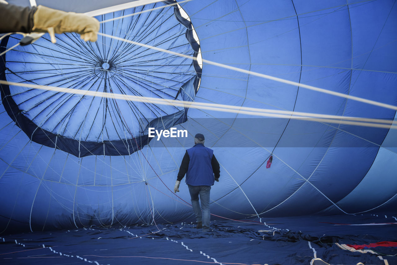 real people, one person, standing, lifestyles, full length, leisure activity, men, day, rear view, holding, women, balloon, occupation, blue, protection, nature, shape, air vehicle