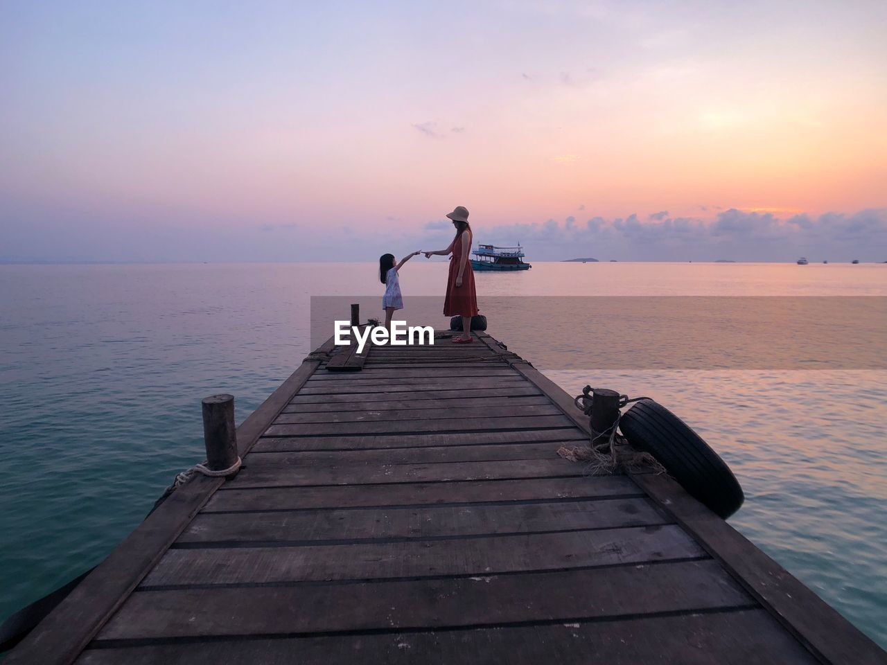 Side View Of Mother With Daughter Standing On Pier Over Sea Against Sky During Sunset