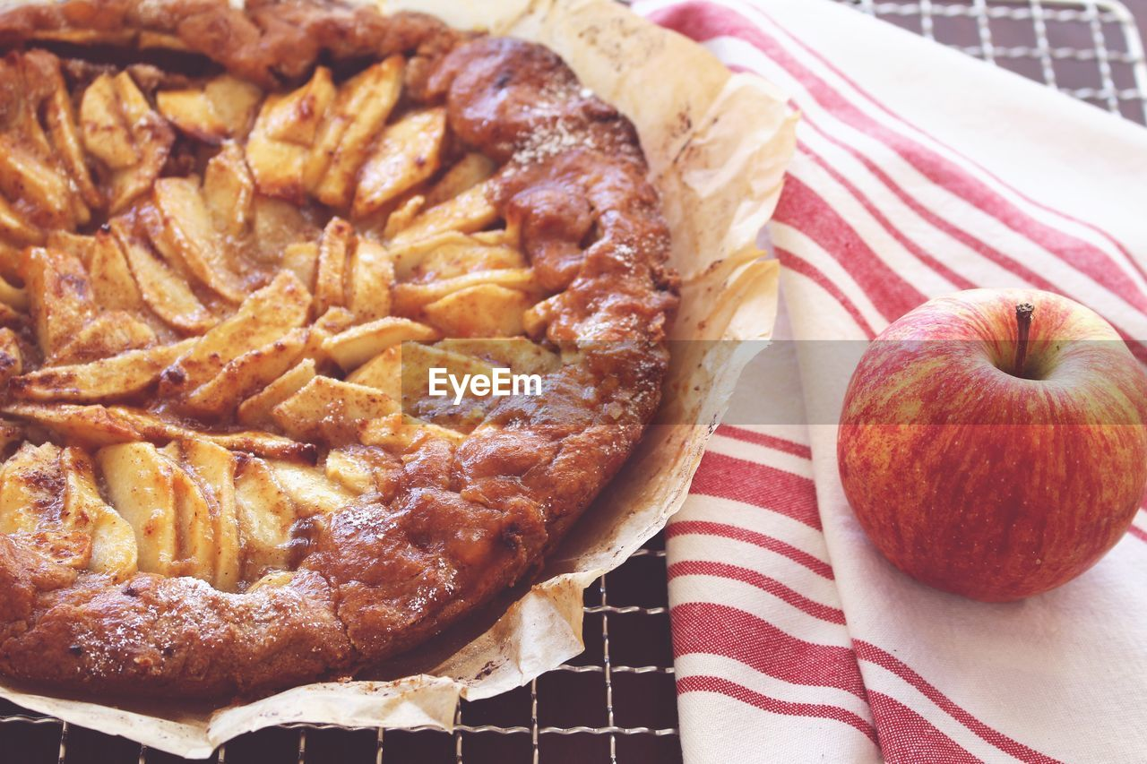 High angle view of pie with apple and napkin on cooling rack