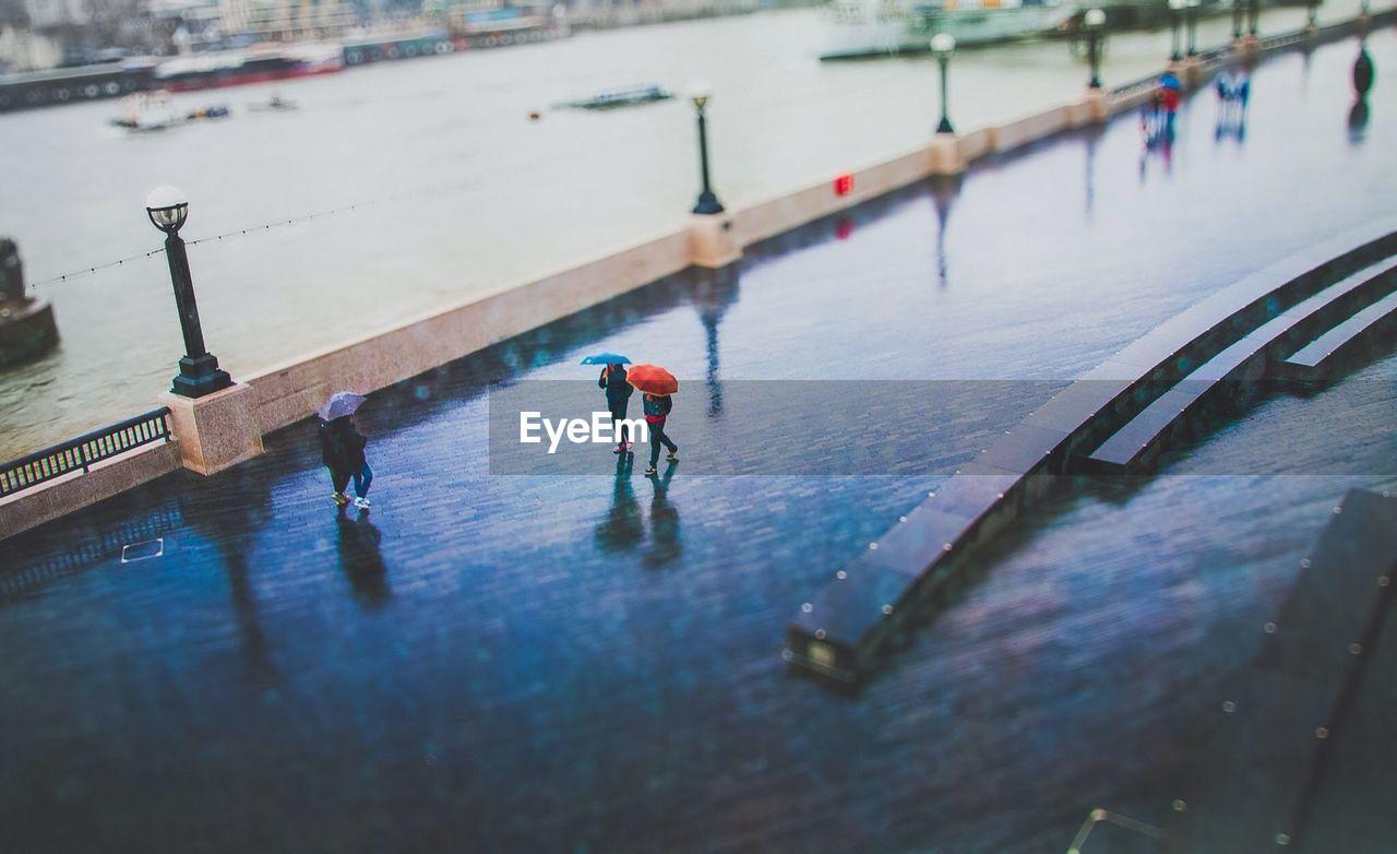 Tilt-Shift Image Of People Walking On Street During Rainy Season